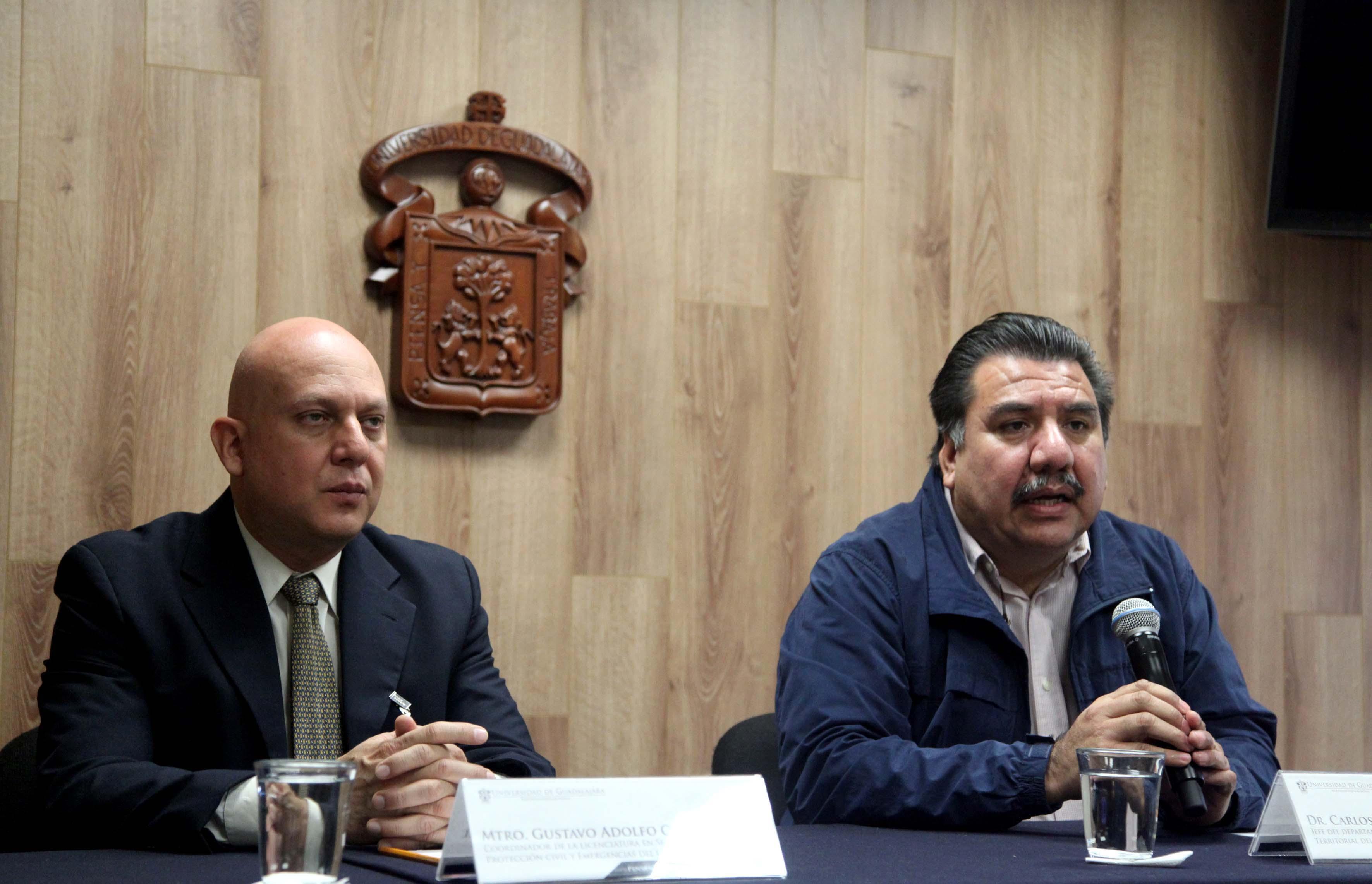 Dos hombres sentados en el estrado del paraninfo UDG
