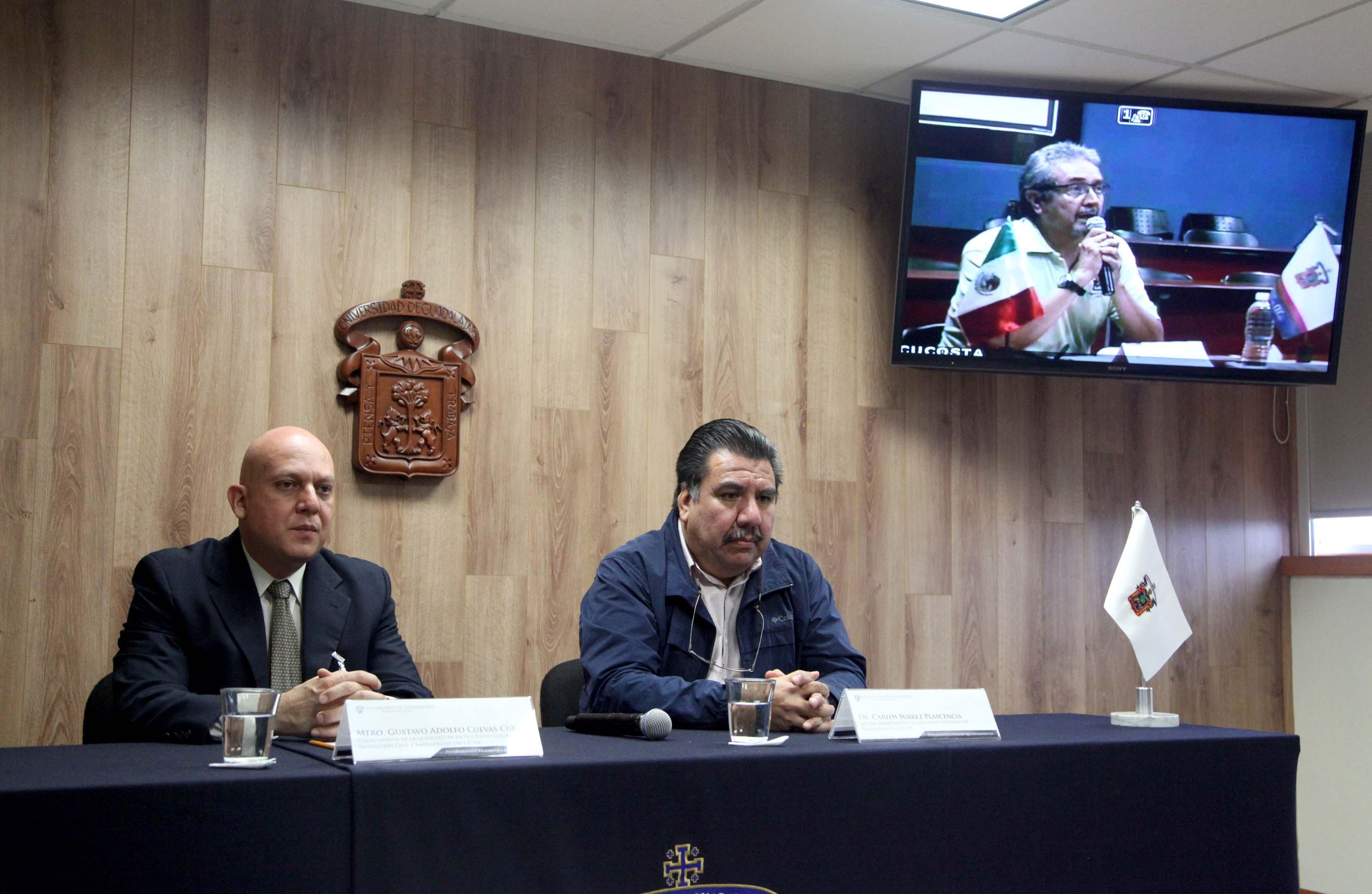 Dos hombres sentados en el estrado del paraninfo UDG, pantalla en la esquina superior derecha