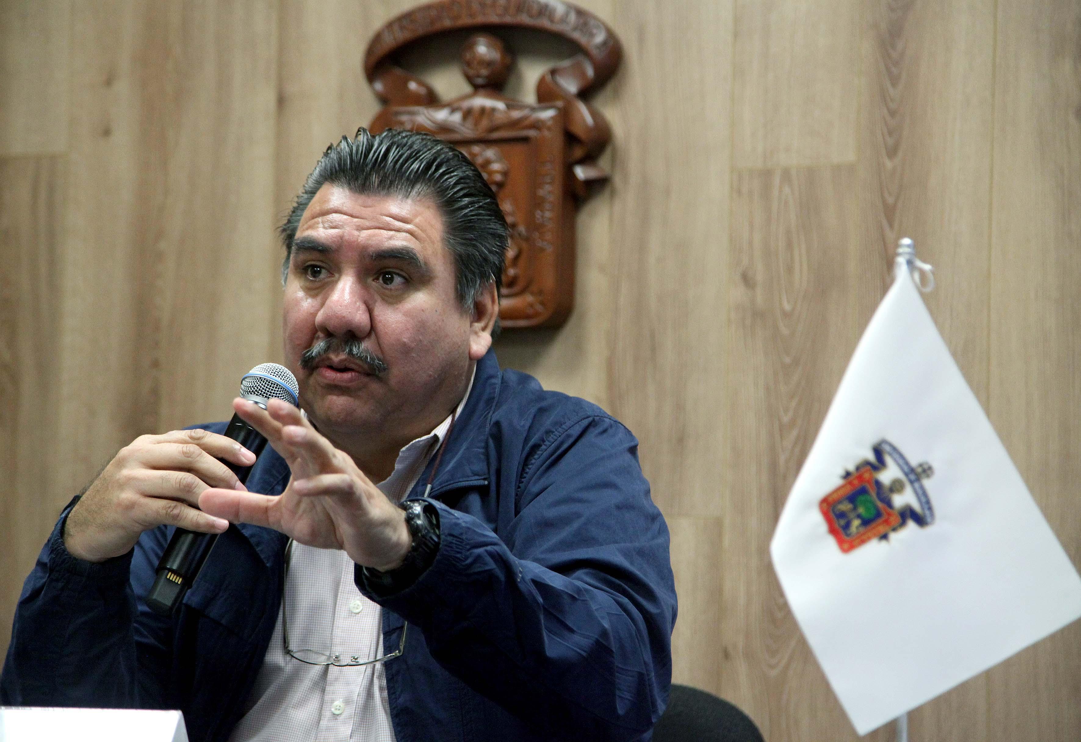 Hombre hablando por micrófono expresándose con las manos