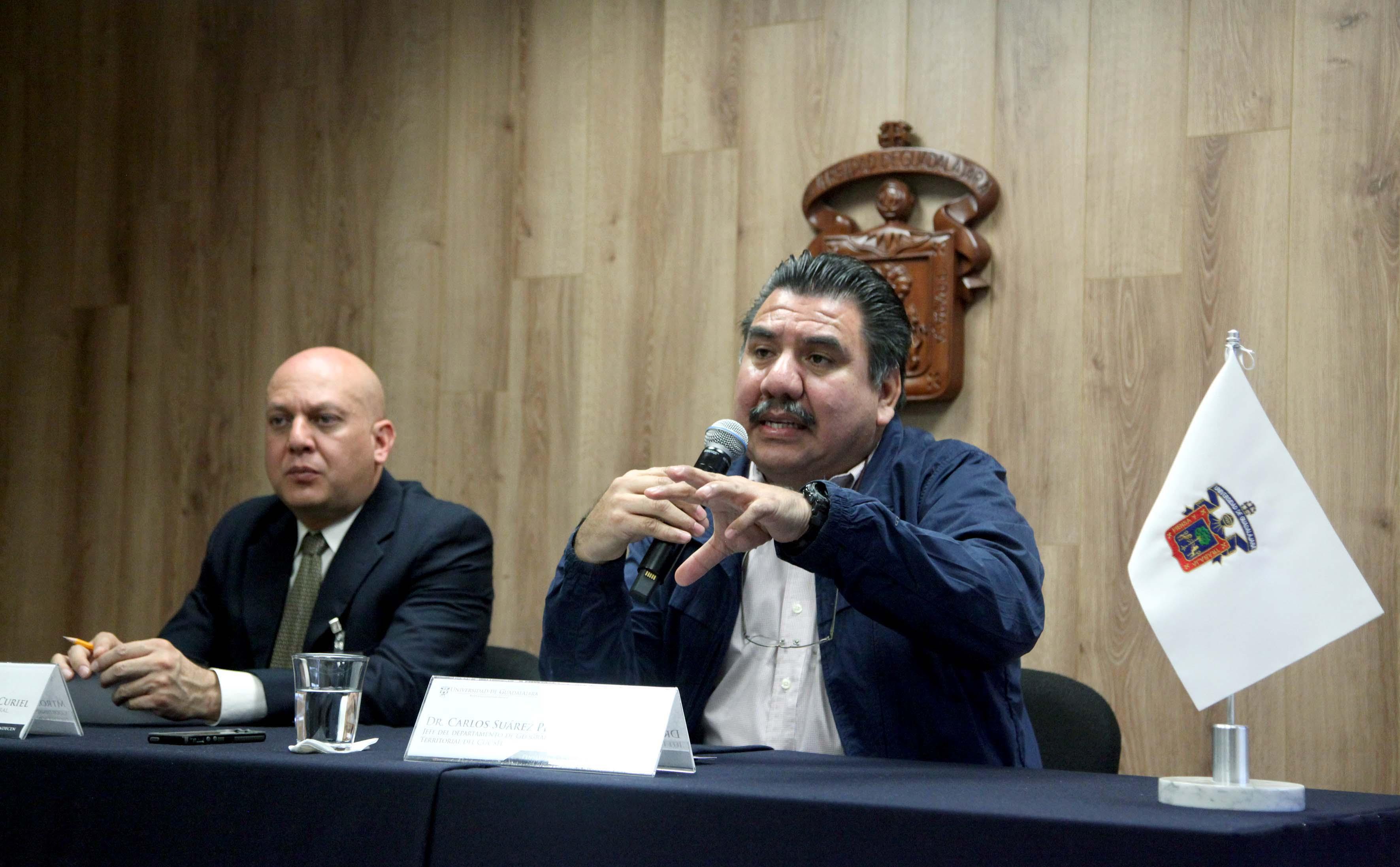 Dos hombres sentados en el estrado de paraninfo UDG uno de ellos hablando por micrófono