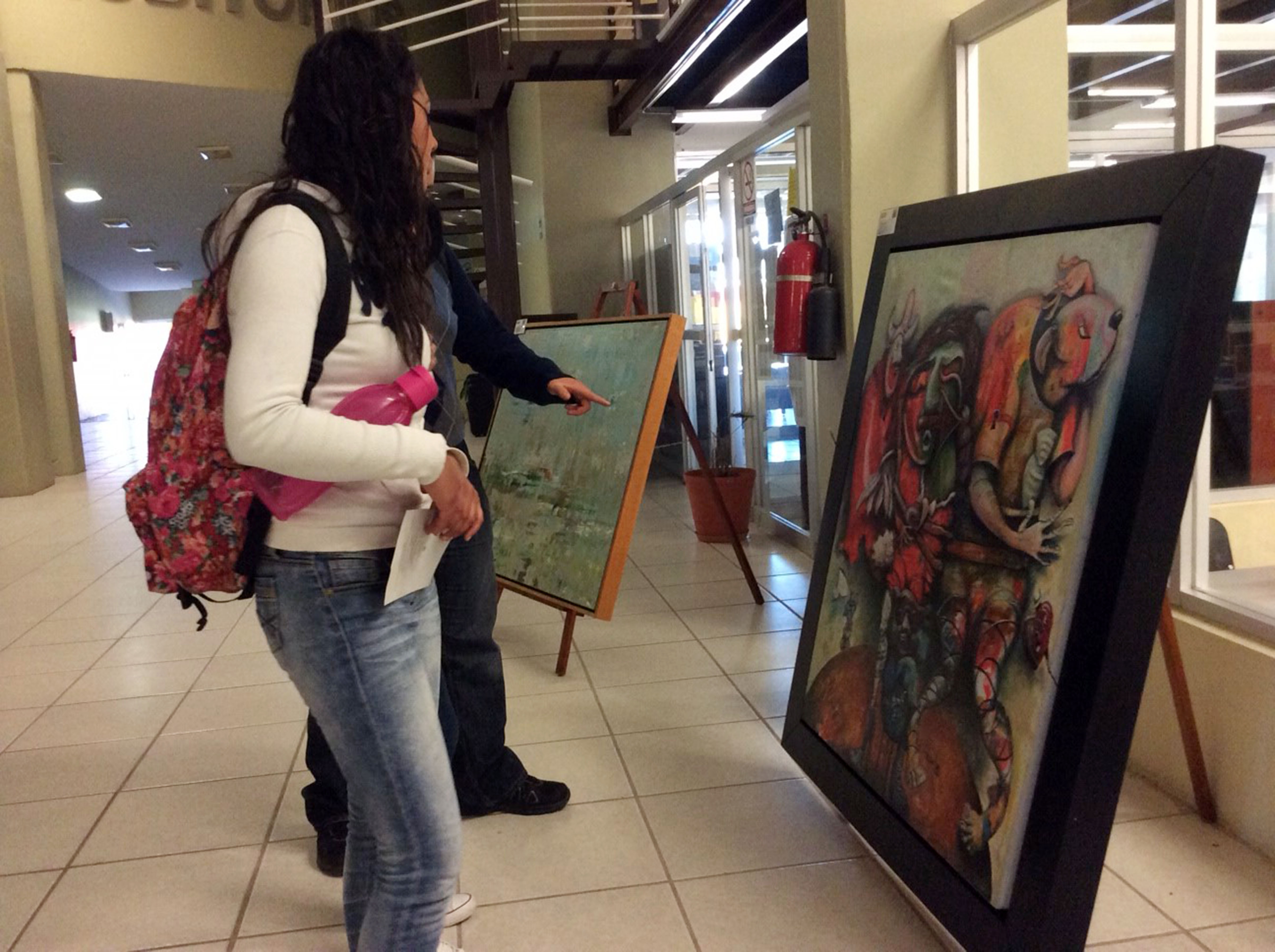 Jovenes admirando pintura abstracta
