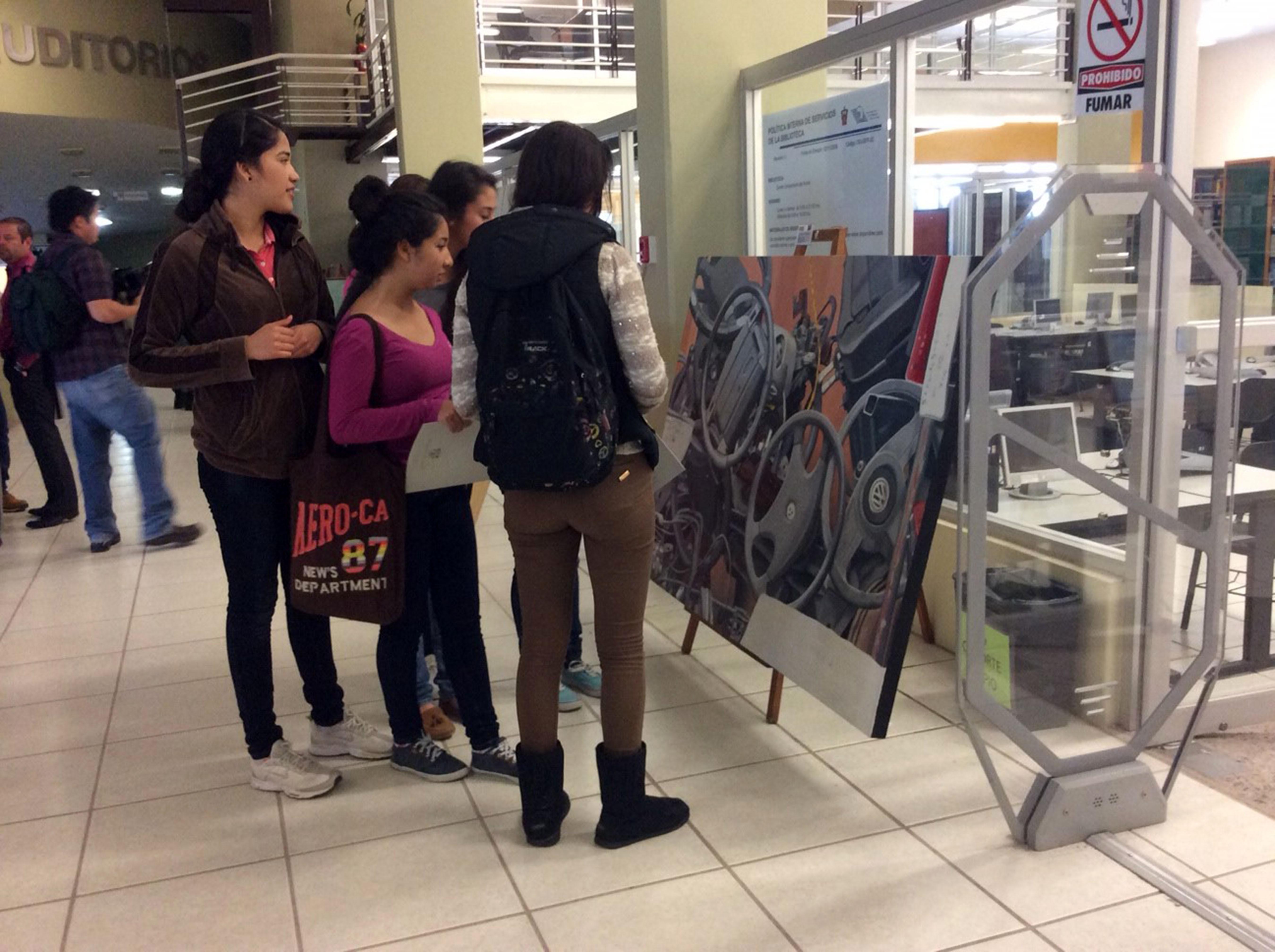 Jovenes Admirando pintura compuesta de volantes de autos y otras autopartes