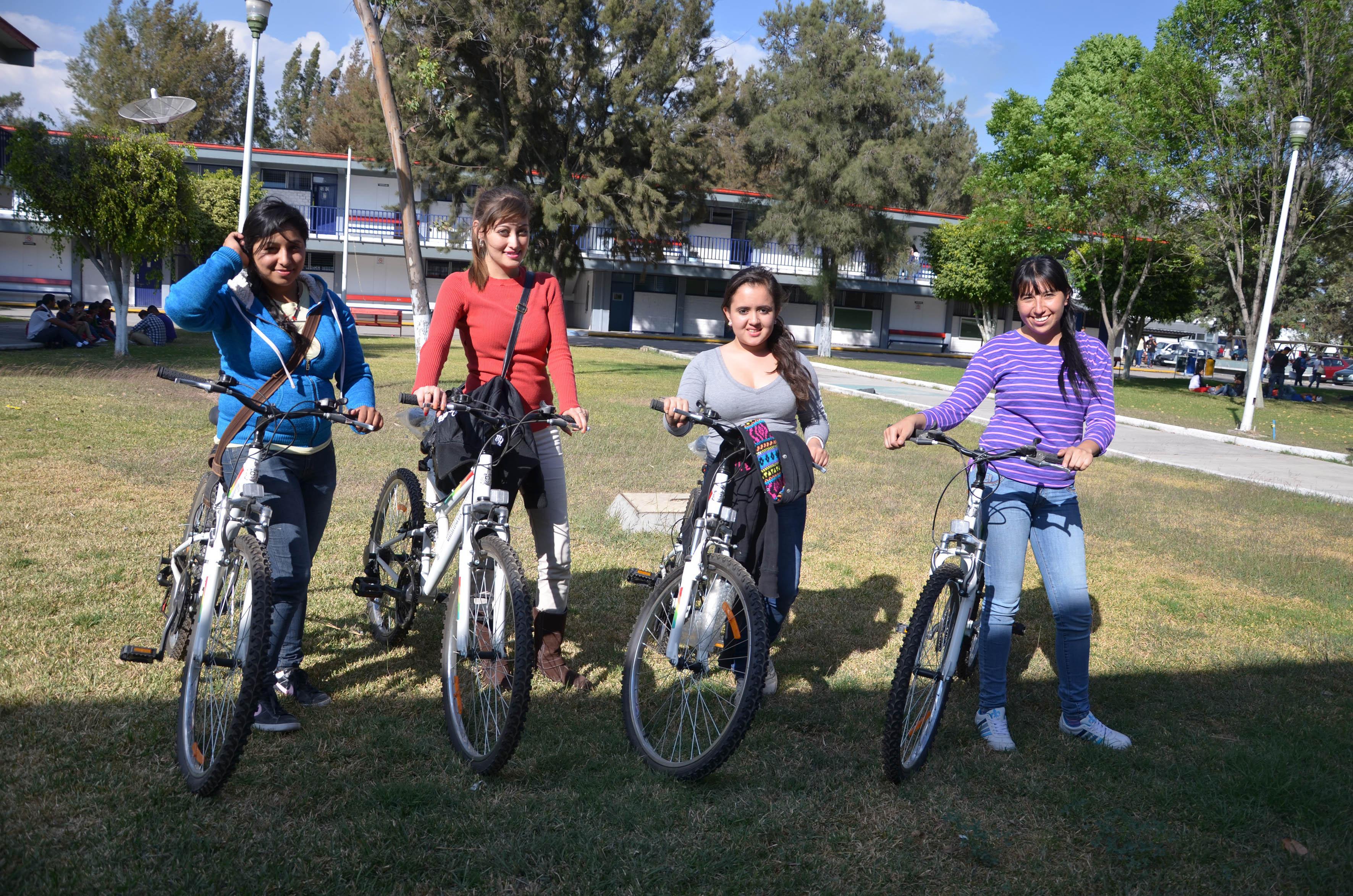 Cuatro alumnas mostrando la bicicleta que recibieron