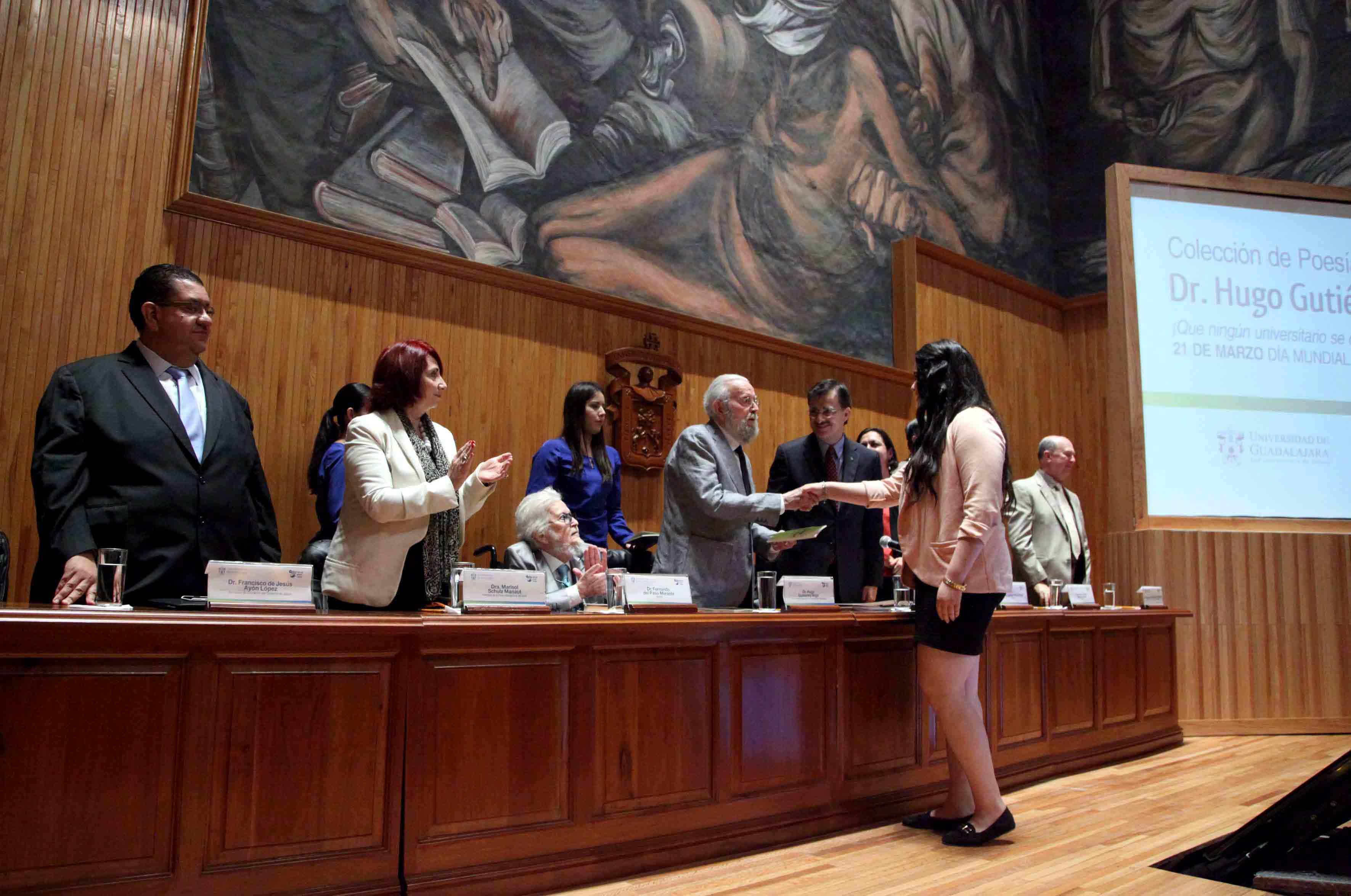 Entrega de ejemplar del primer título de la colección presentada a Itzel Bravo Calzada de la Preparatoria de Puerto Vallarta, ganadora de FIL Joven 2014 en la categoría de Poesía, por partre del Dr. Hugo Gutiérrez Vega.