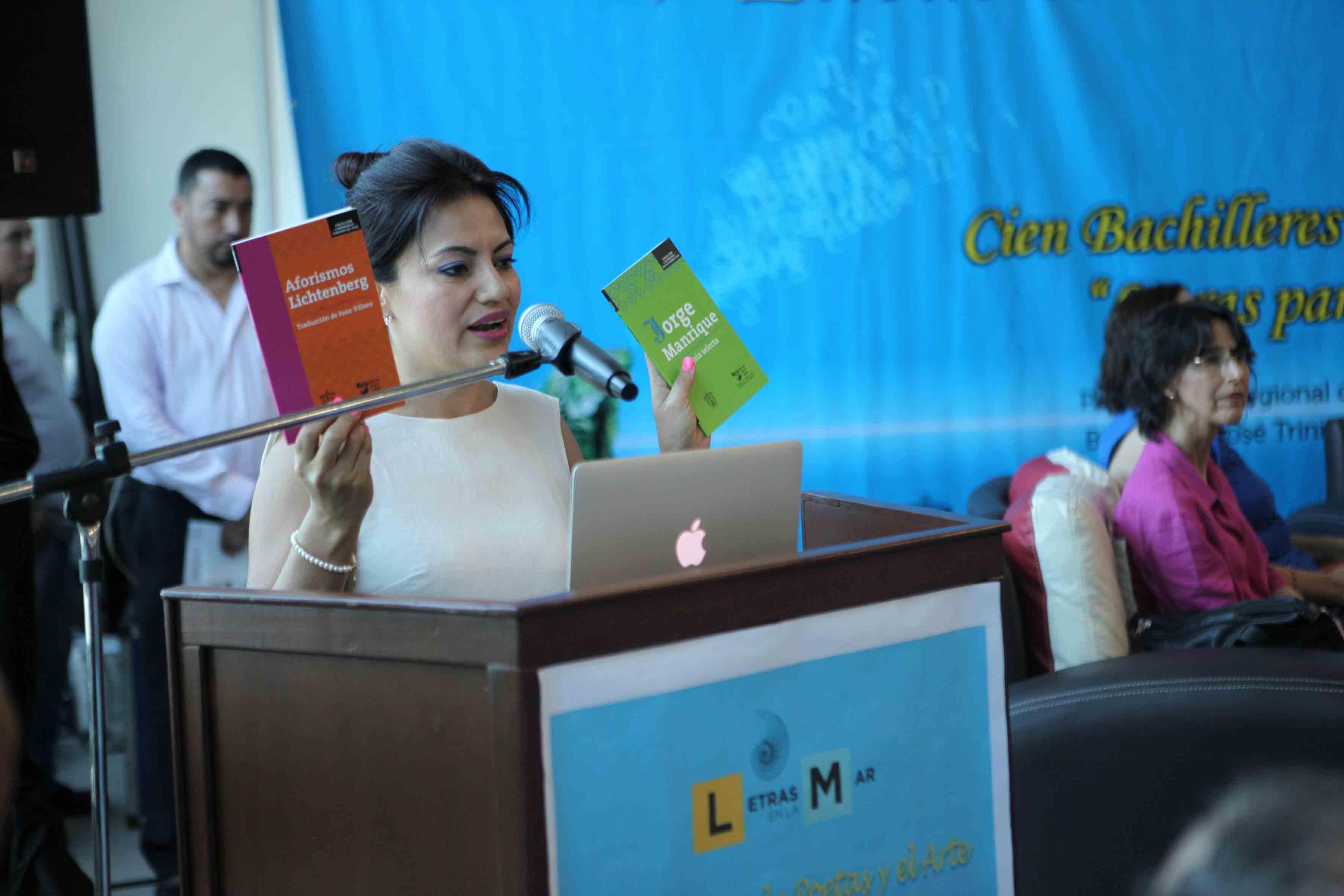 Dra. Patricia Rosas Chavez hablandp frente al microfono y mostrando dos libros