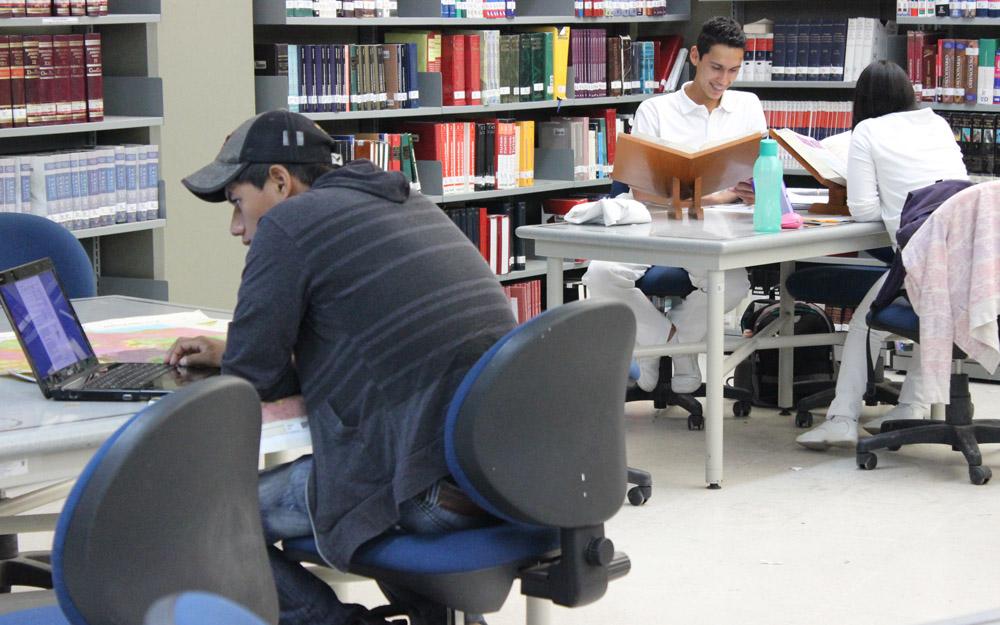 Joven frente a una computadora portatil en una biblioteca