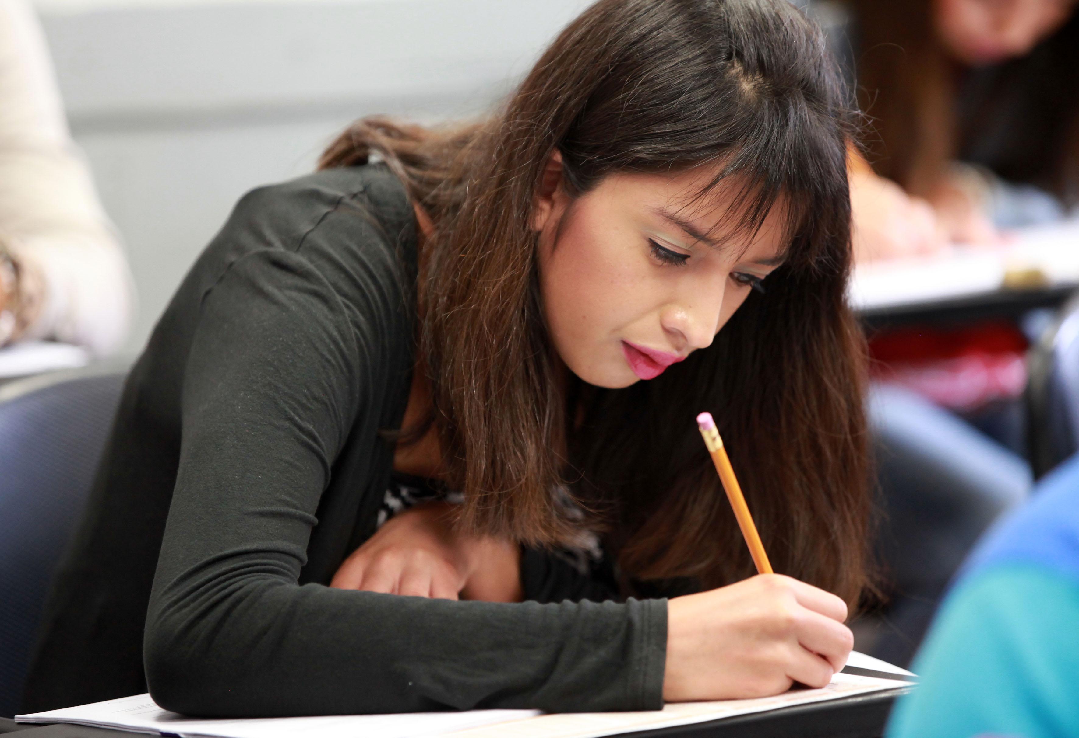 Alumna en aula de clases escribiendo