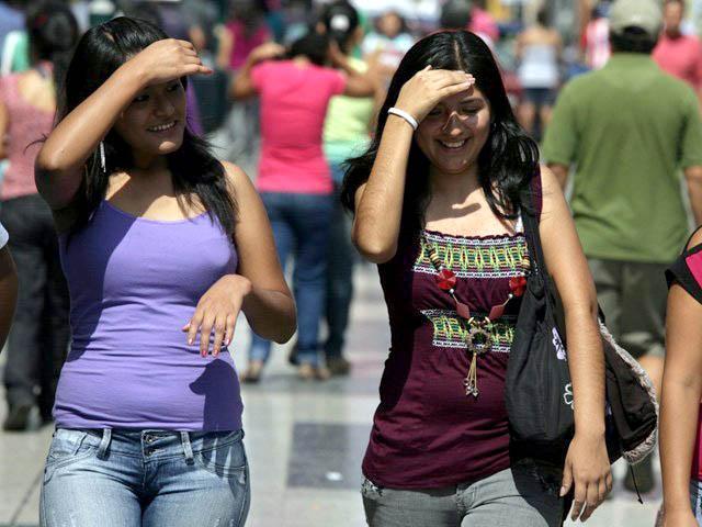 Mujeres caminando y tapándose con la mano el sol.