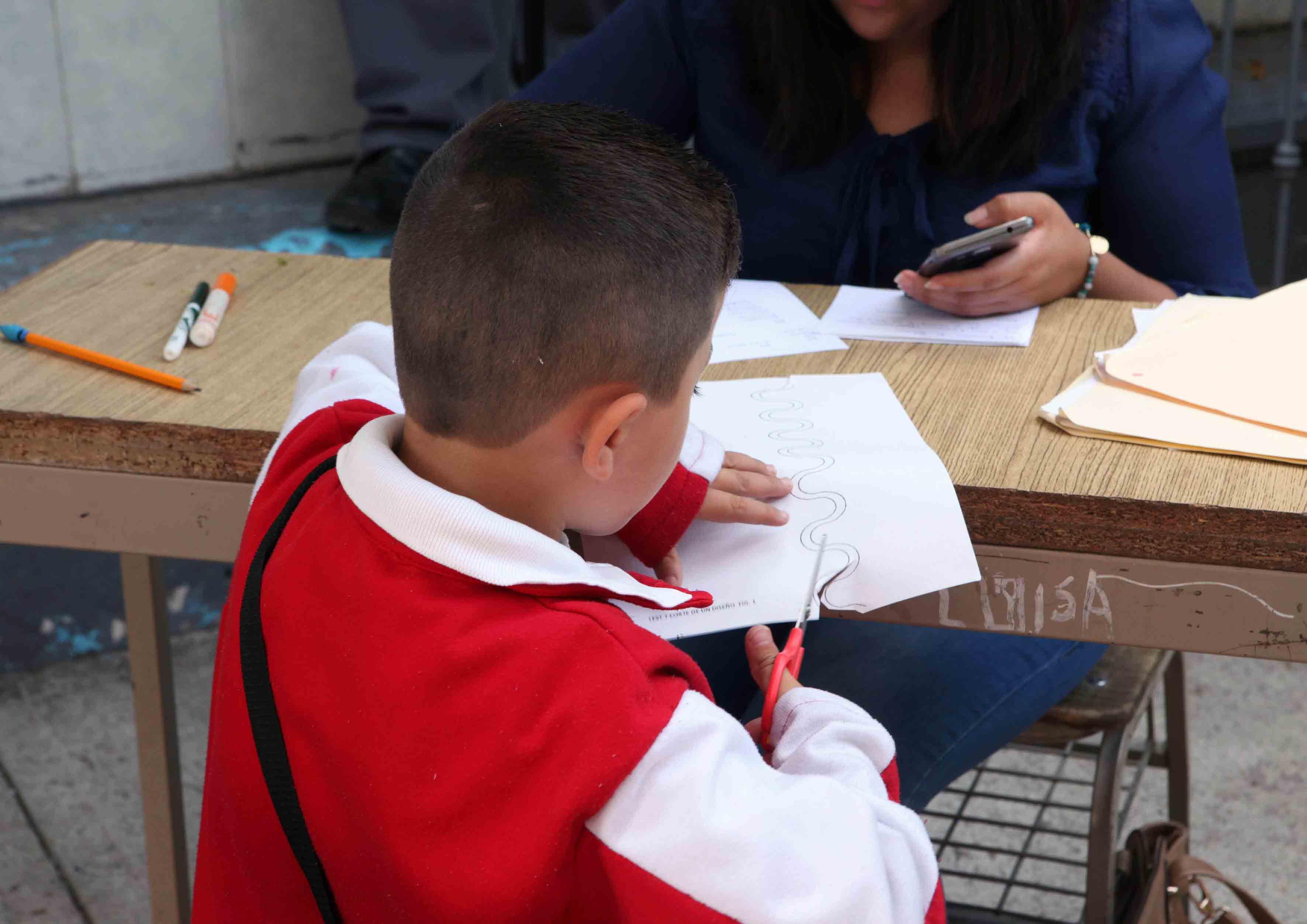 Niño realizando actividades escolares en mesa de trabajo