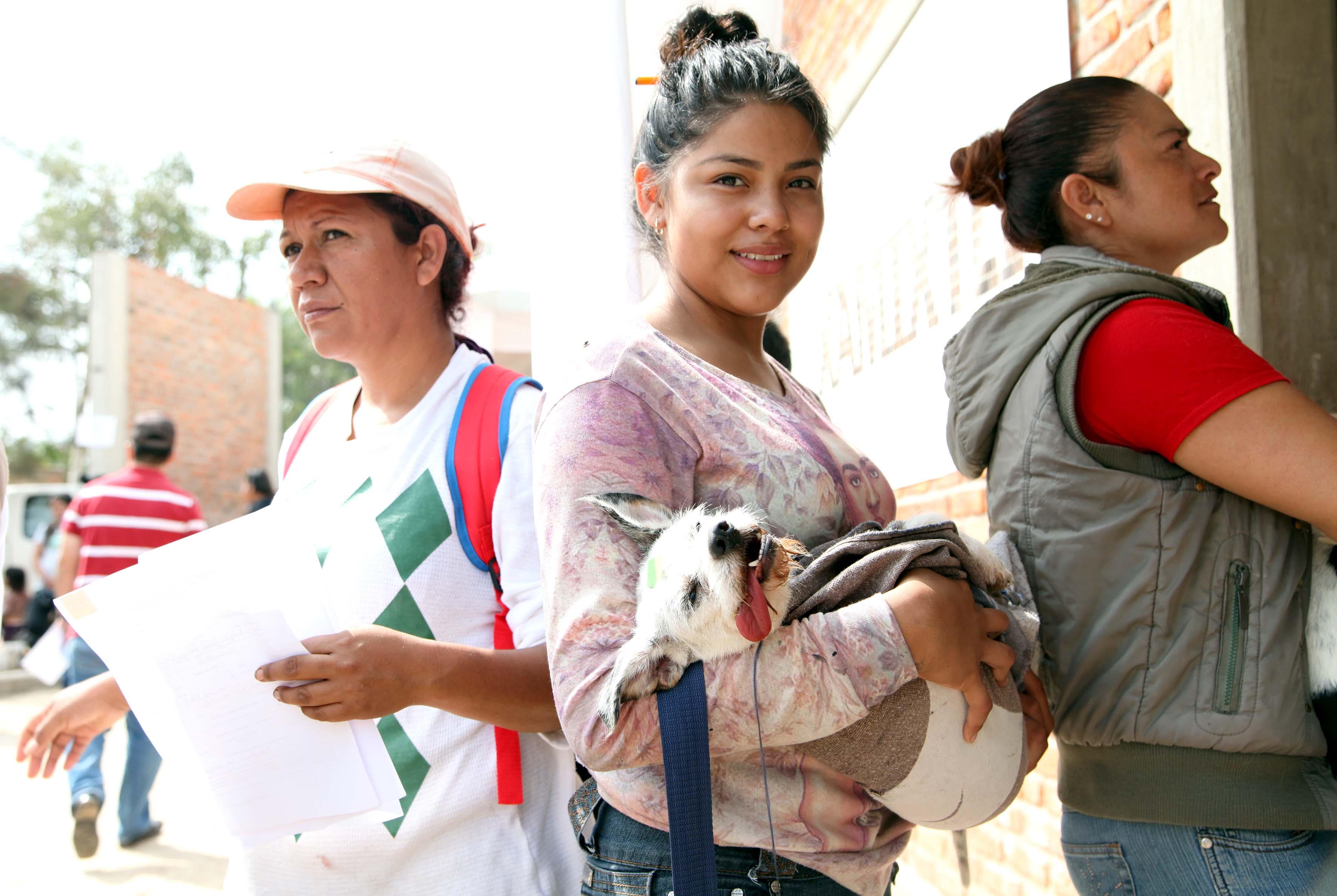 Mujer cargando a su mascota despues de ser esterelizada