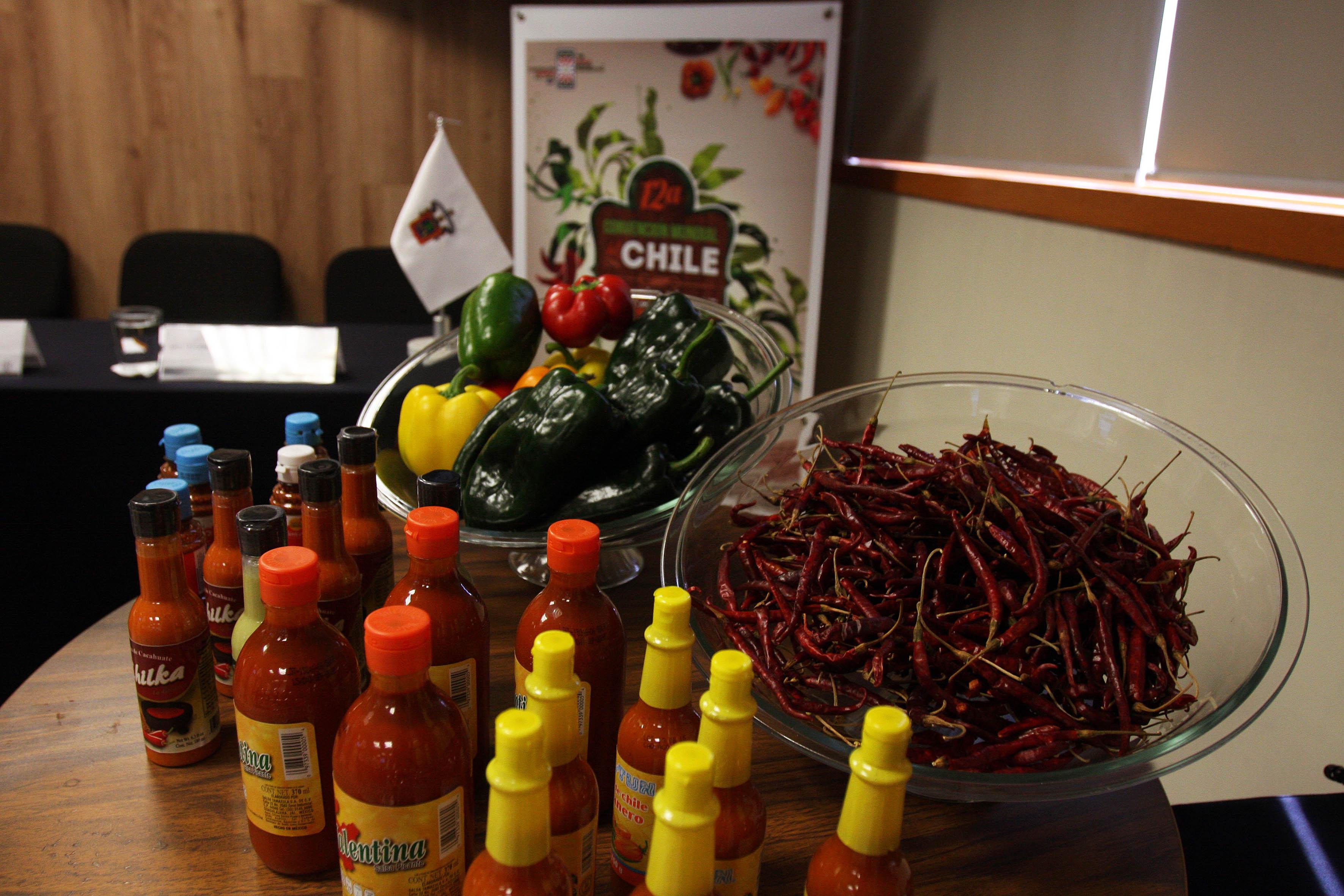 Canastas con chiles frescos y secos y diferentes salsas embotelladas.