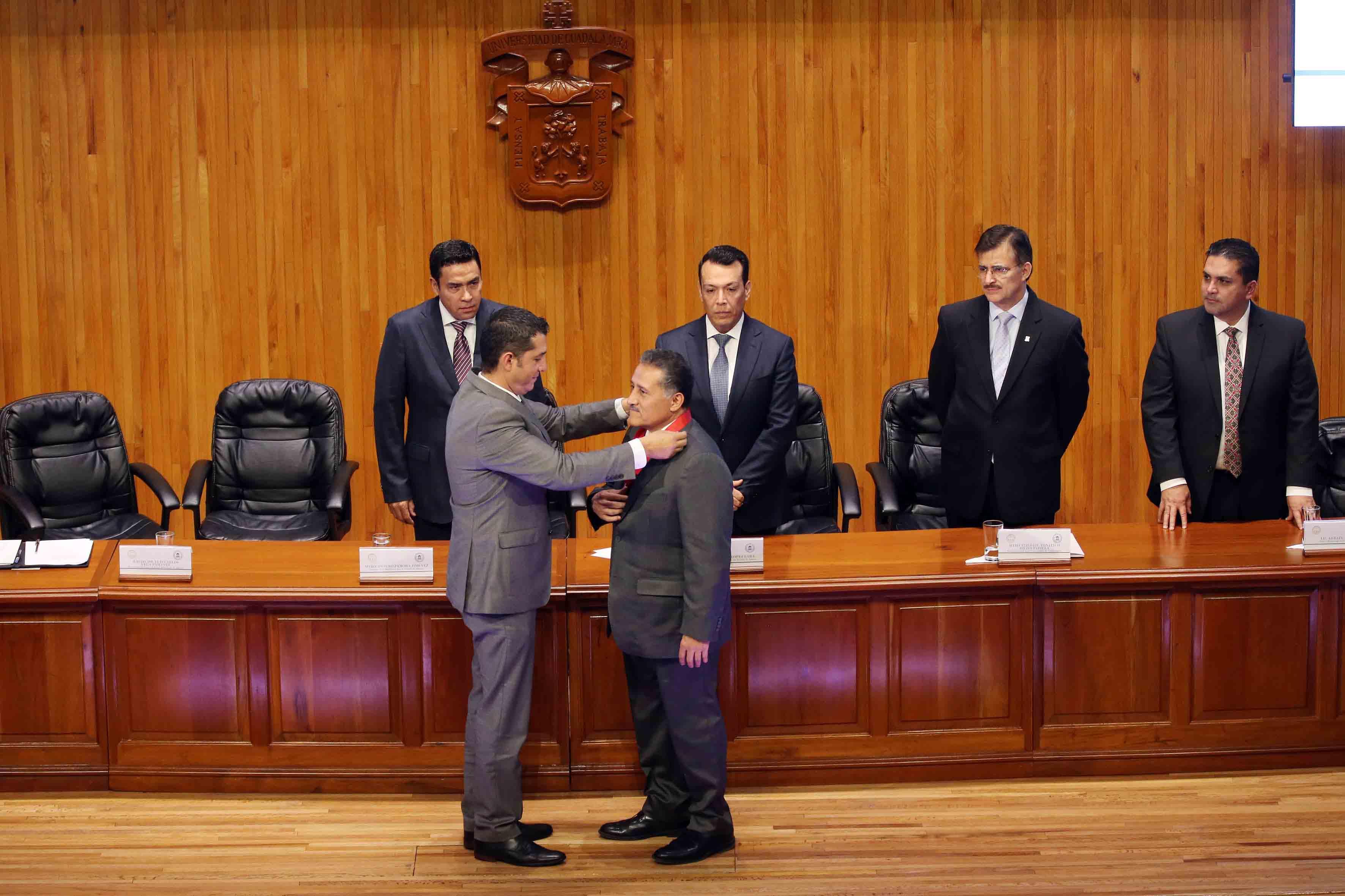 Mtro. Luis Gustavo Padilla Montes, presidente de MABA capítulo México, colocando la medalla al galardonado, el maestro y senador Arturo Zamora Jiménez.
