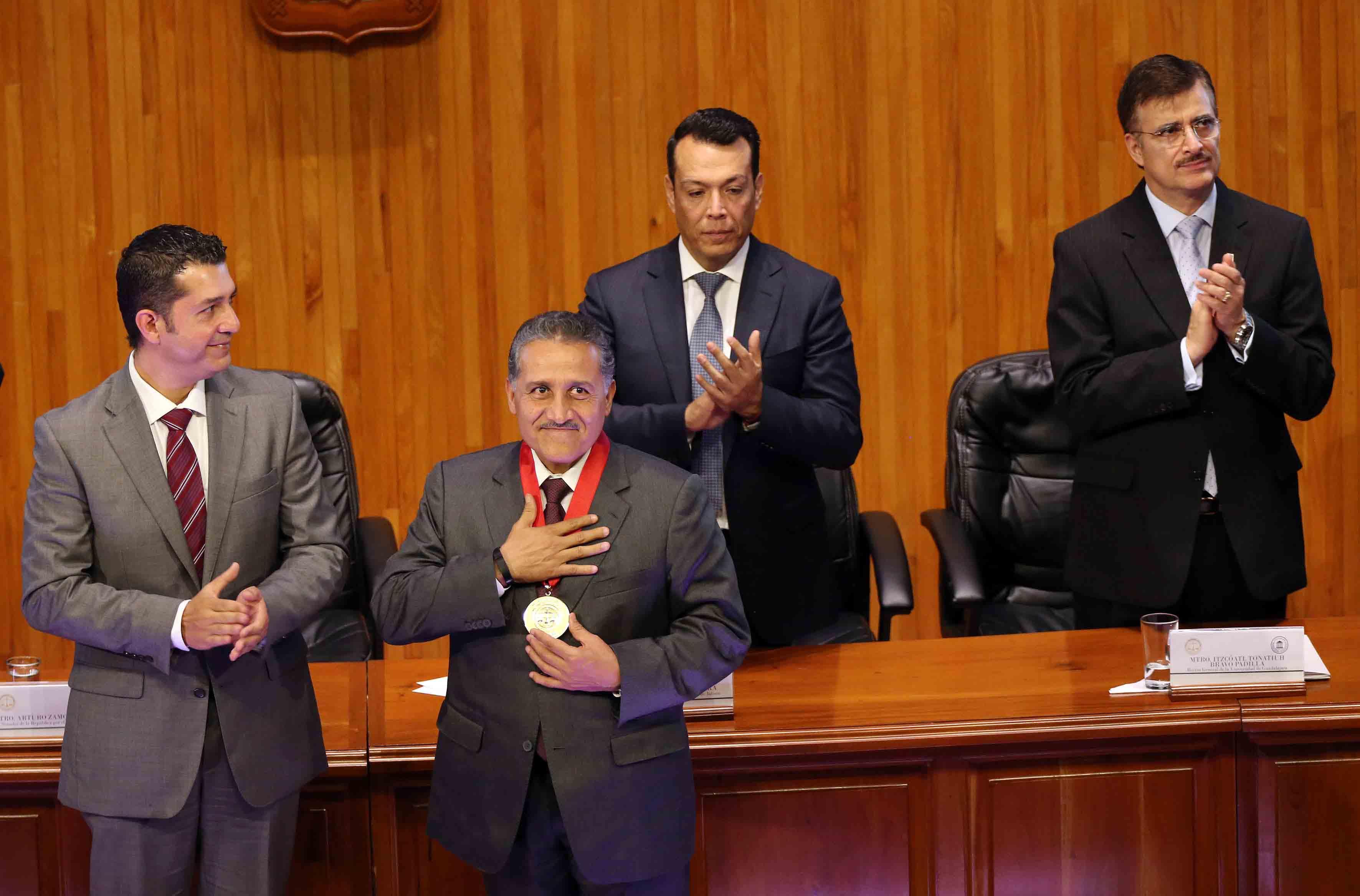 El maestro y senador Arturo Zamora Jiménez, con medalla en cuello, y mano en pecho, agradeciendo al público asistente al Paraninfo Enrique Díaz de León.