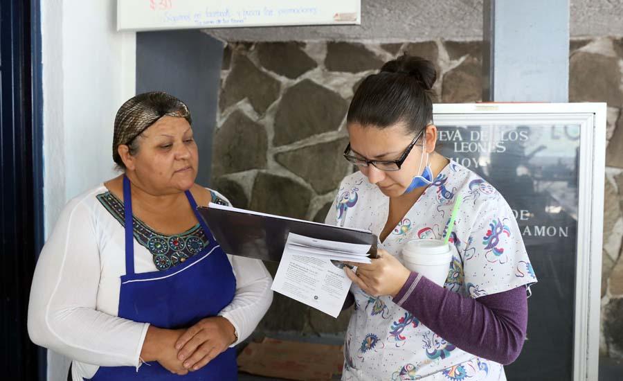 Personal de salud encuestando a una mujer