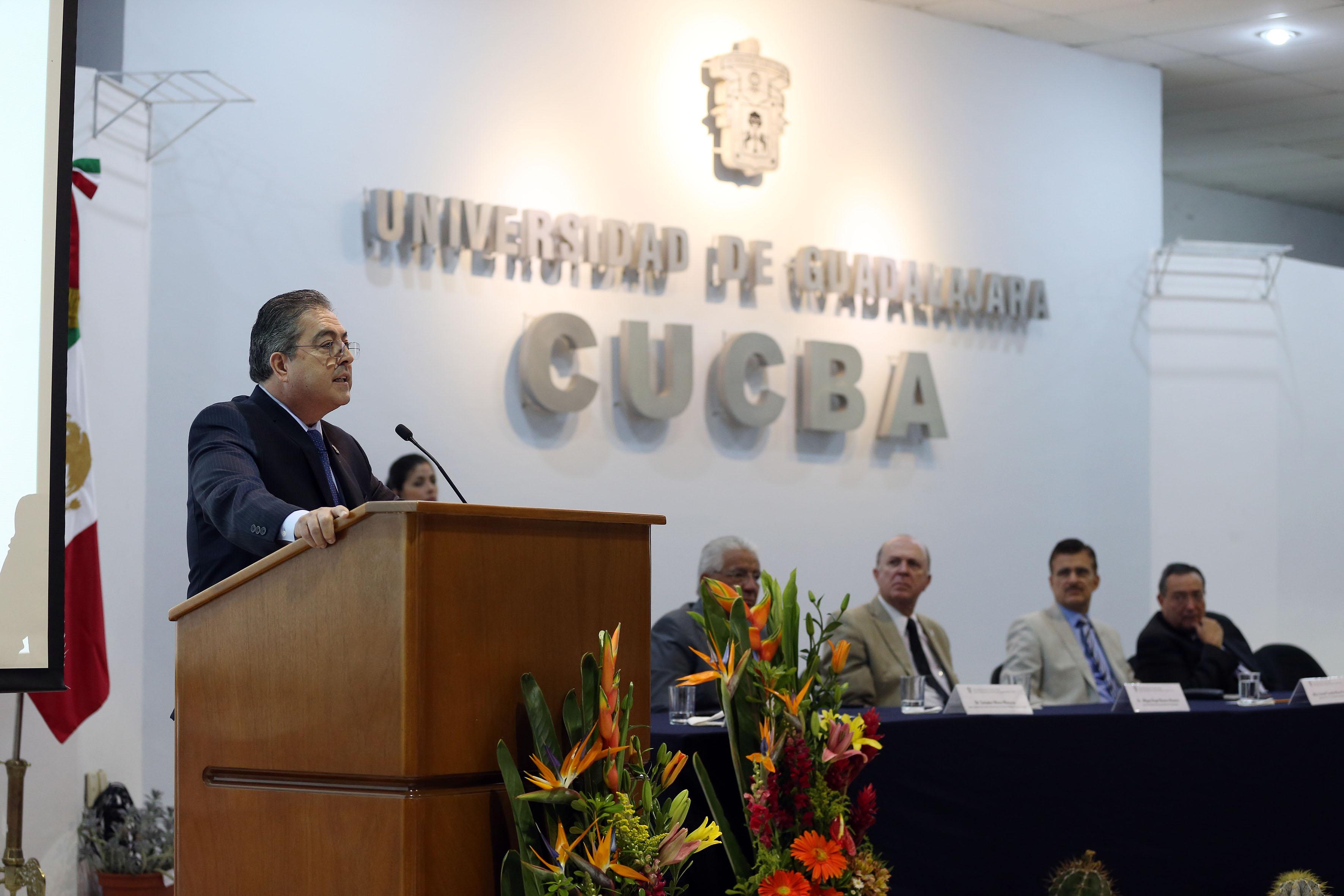 Doctor Carlos Beas Zárate, Rector del CUCBA, con micrófono en podium, haciendo uso de la palabra.