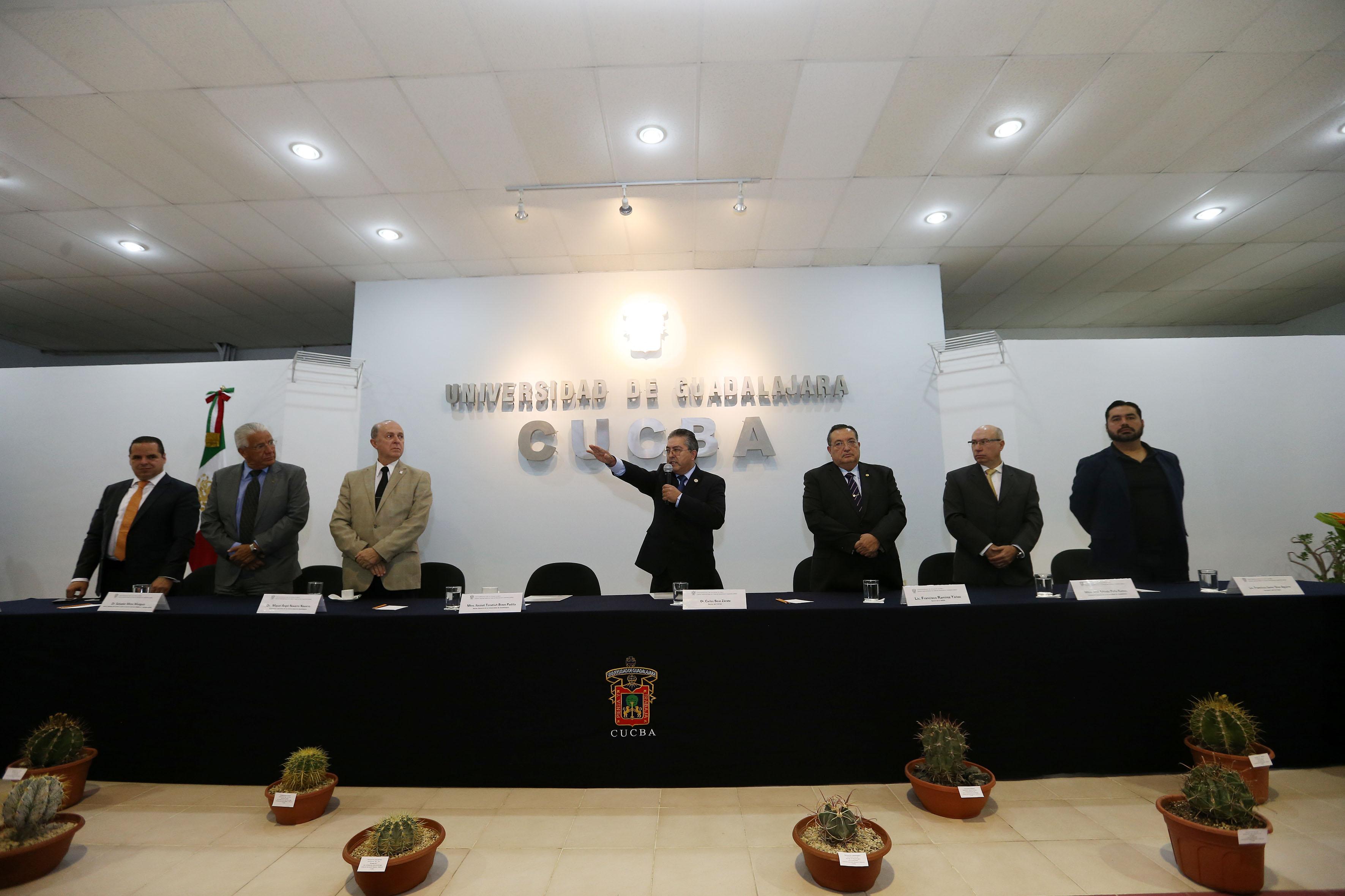 Doctor Carlos Beas Zárate, Rector del CUCBA, levantando la mano y con micrófono en mano, haciendo toma de protesta a su cargo como Rector del CUCBA.