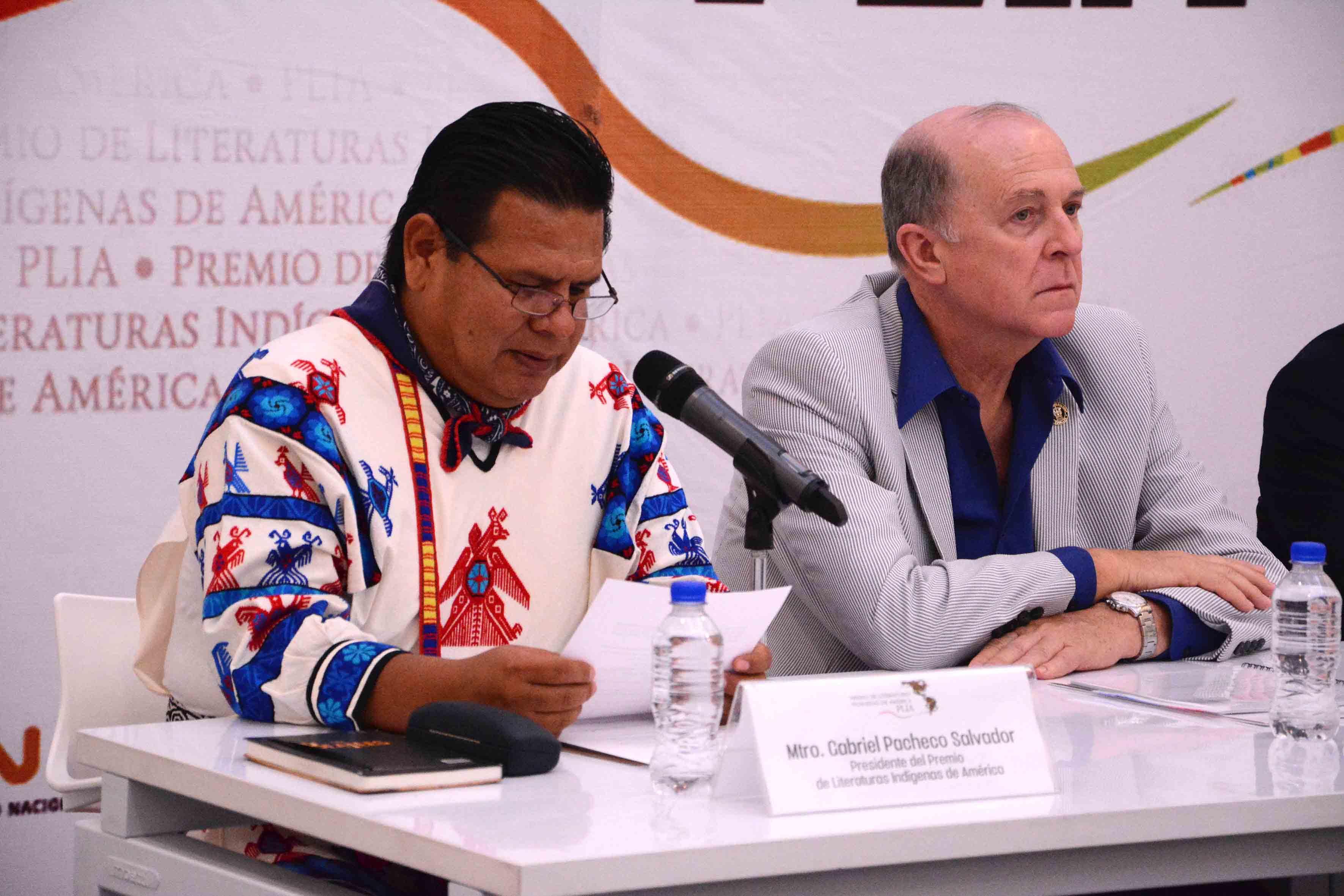 Maestro Gabriel Pacheco Salvador, presidente de la Comisión Interinstitucional de PLIA, con documento en manos y micrófono en mesa de panel, haciendo uso de la palabra.