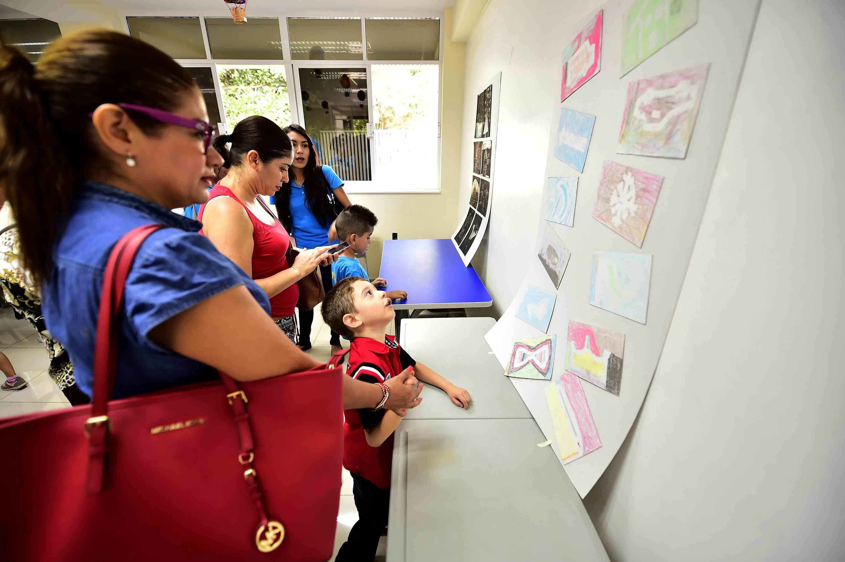 Padres de familia vendo dibujos de la exposición