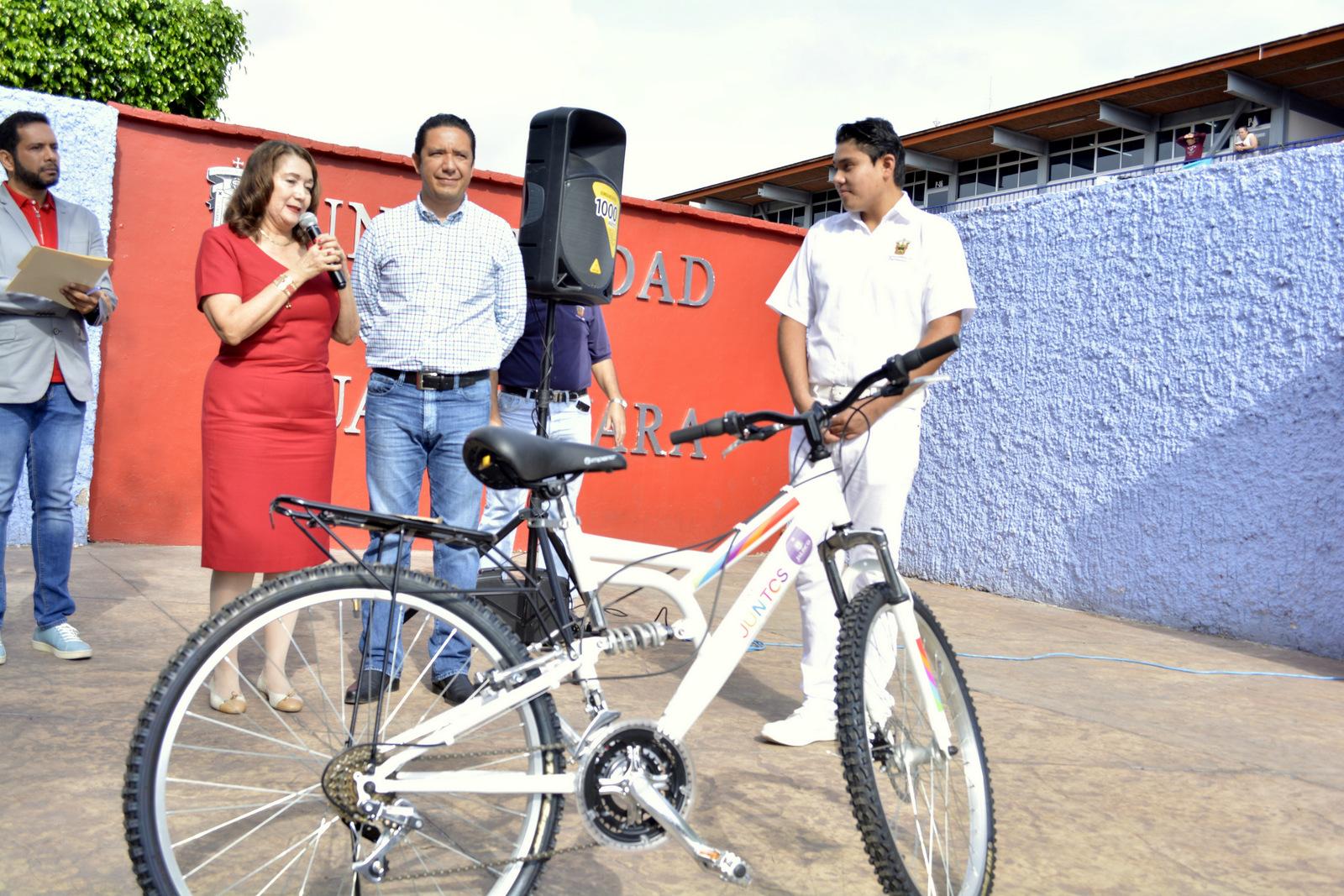 Alumno recibiendo bici de parte de las autoridades universitarias
