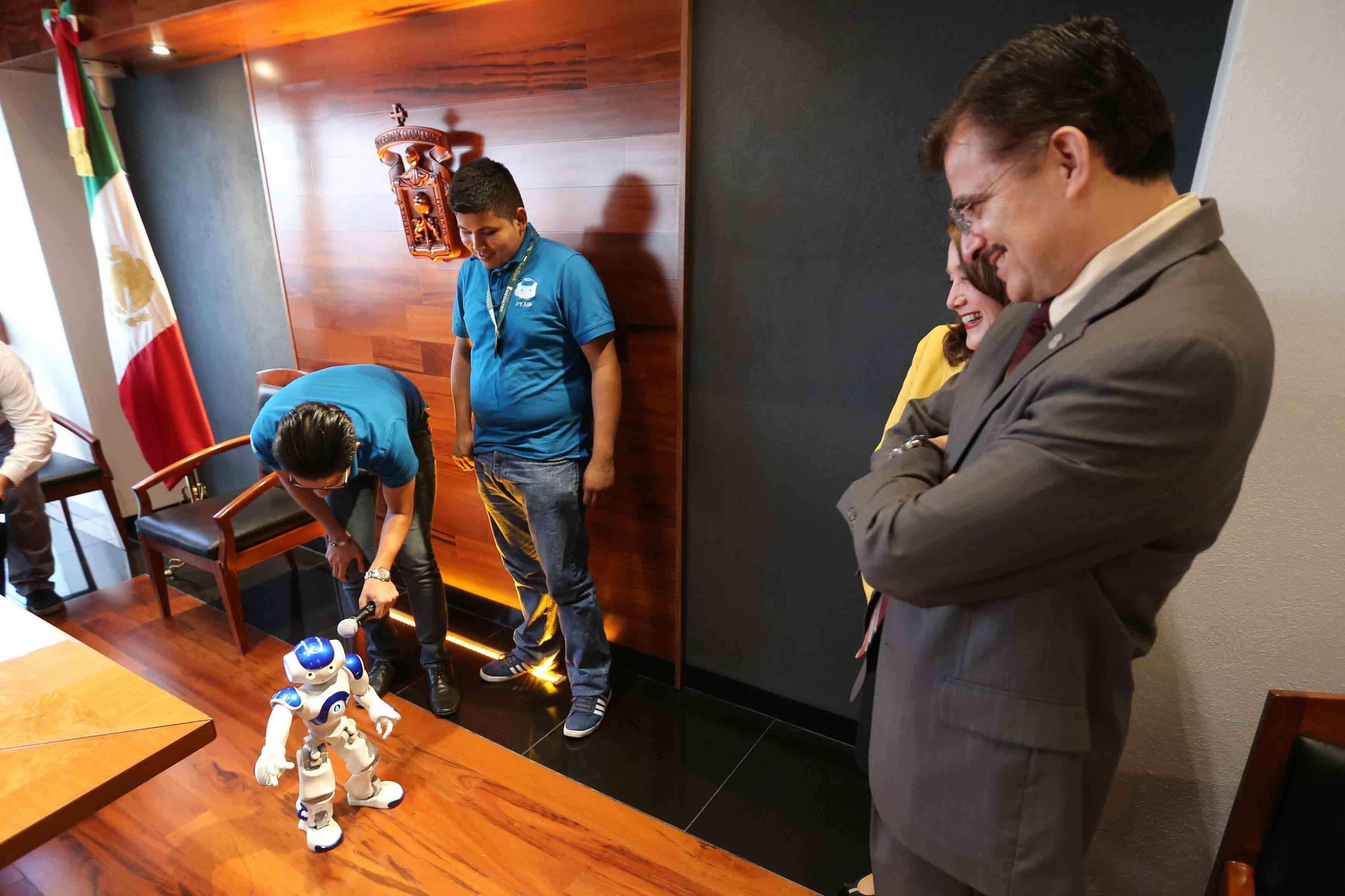 Estudiantes poniendo en función a su nano robot para que el Rector General de la UdeG y la Rectora del CUCSur, Observen lo que hace el mismo.