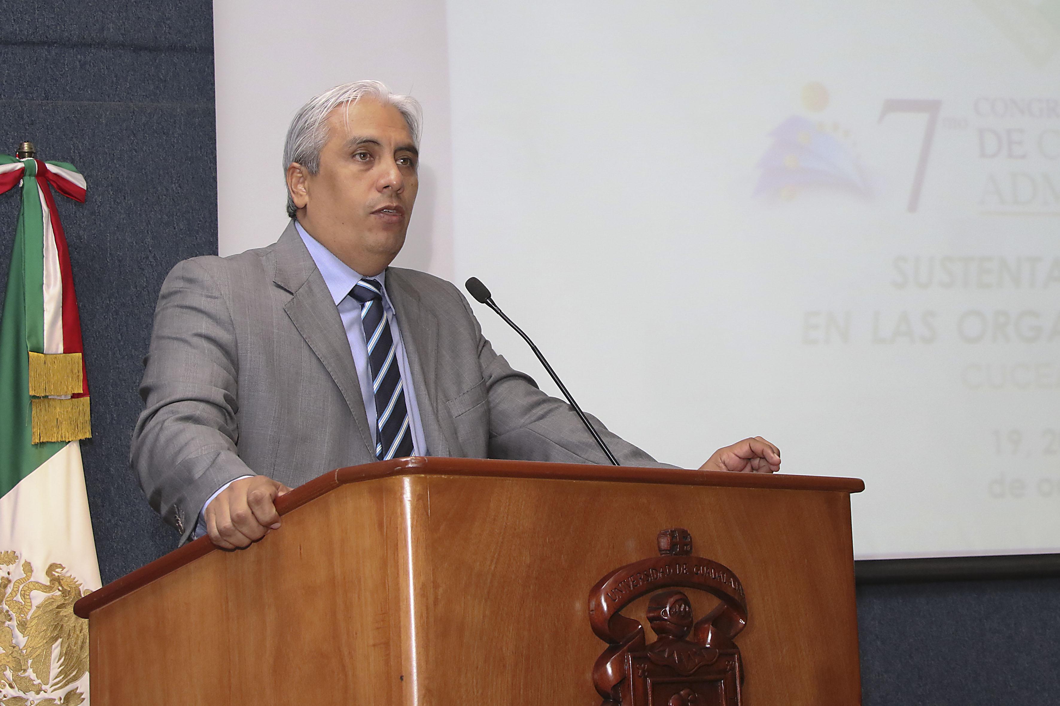 Doctor José Alberto Becerra Santiago, Secretario académico del CUCEA, frente al micrófono
