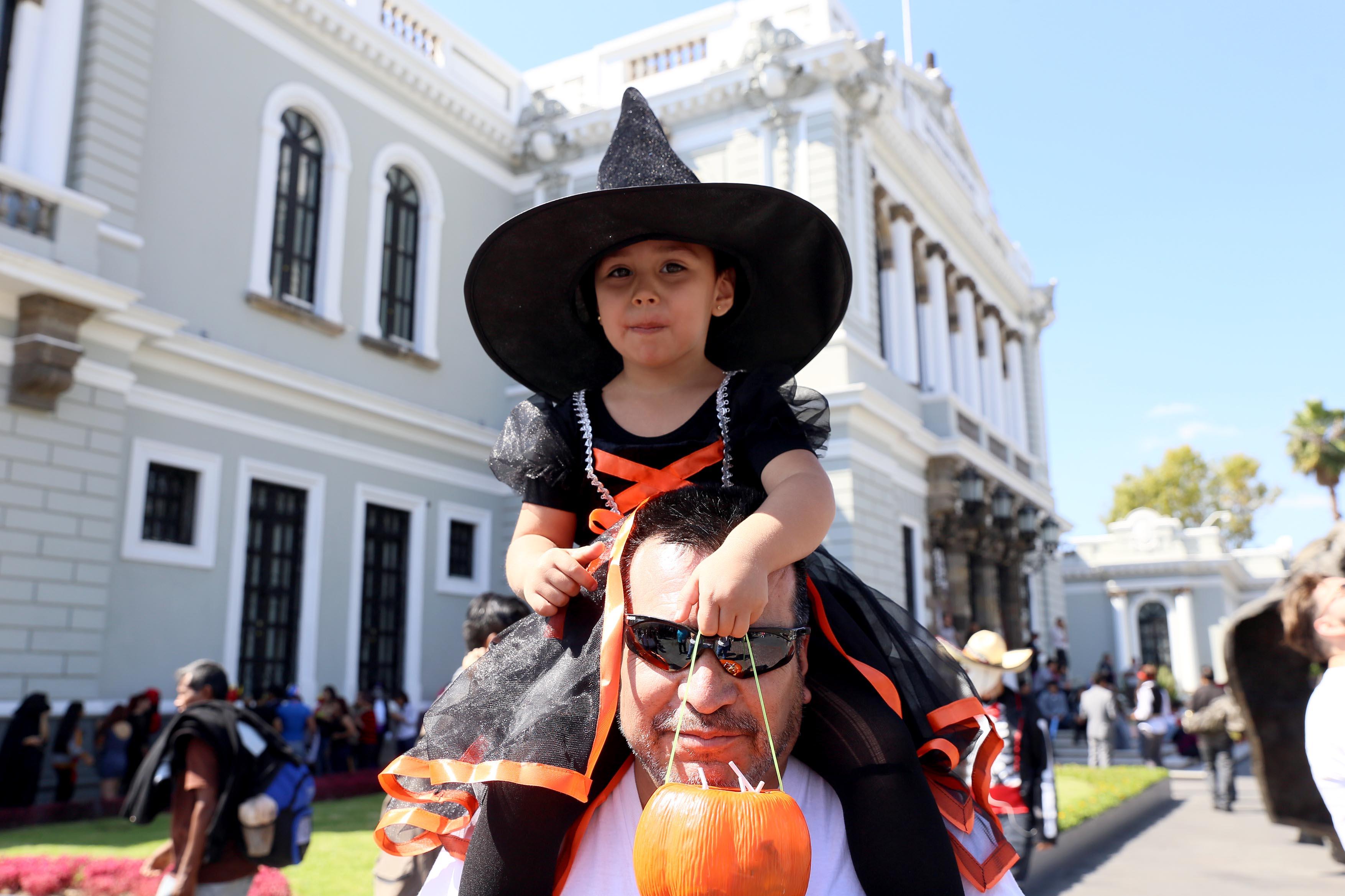 Padre cargando a su hija, disfrazada de bruja y cargando una calabaza
