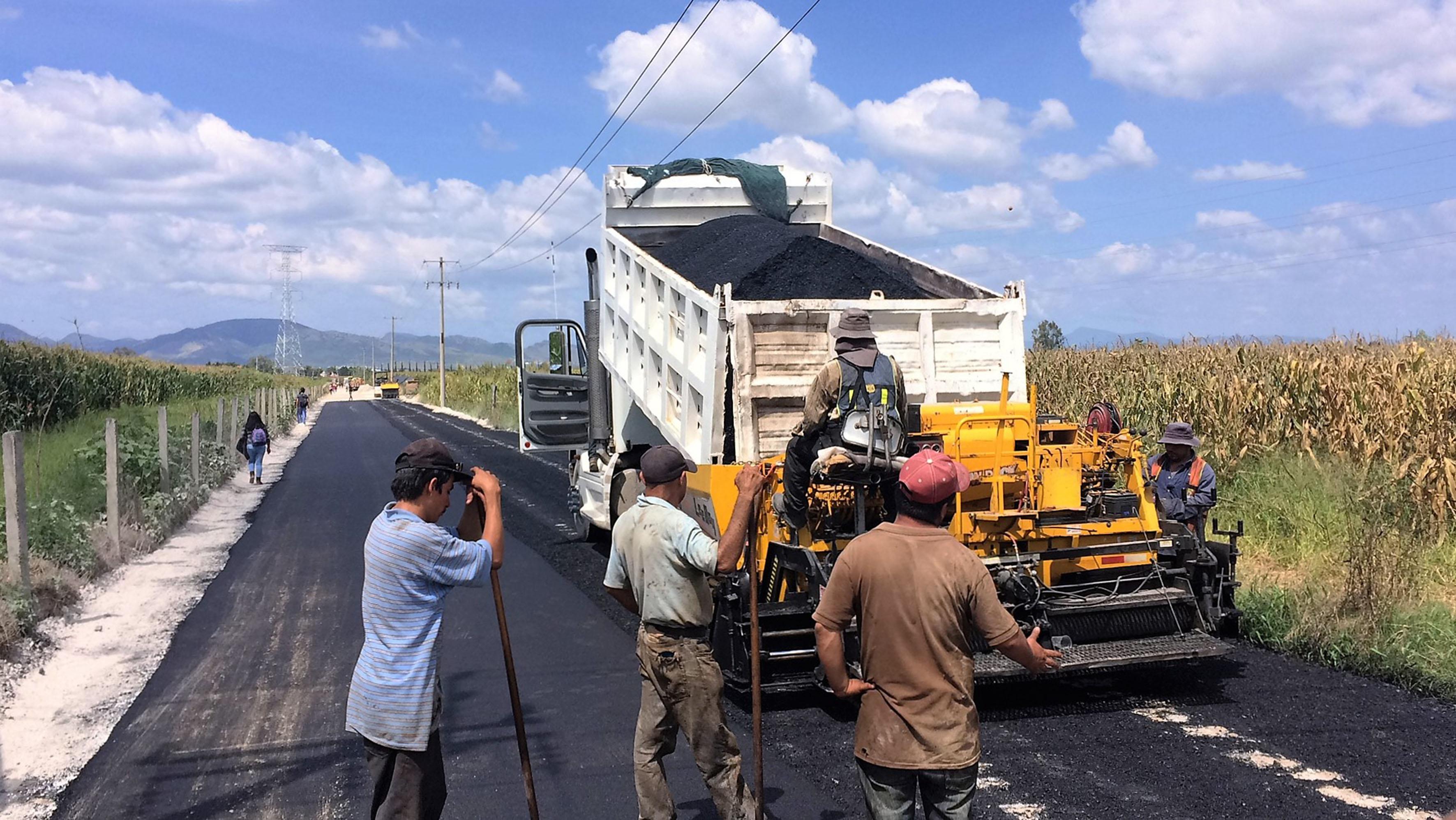 Trabajadores de la obra manipulando la maquina pavimentadora