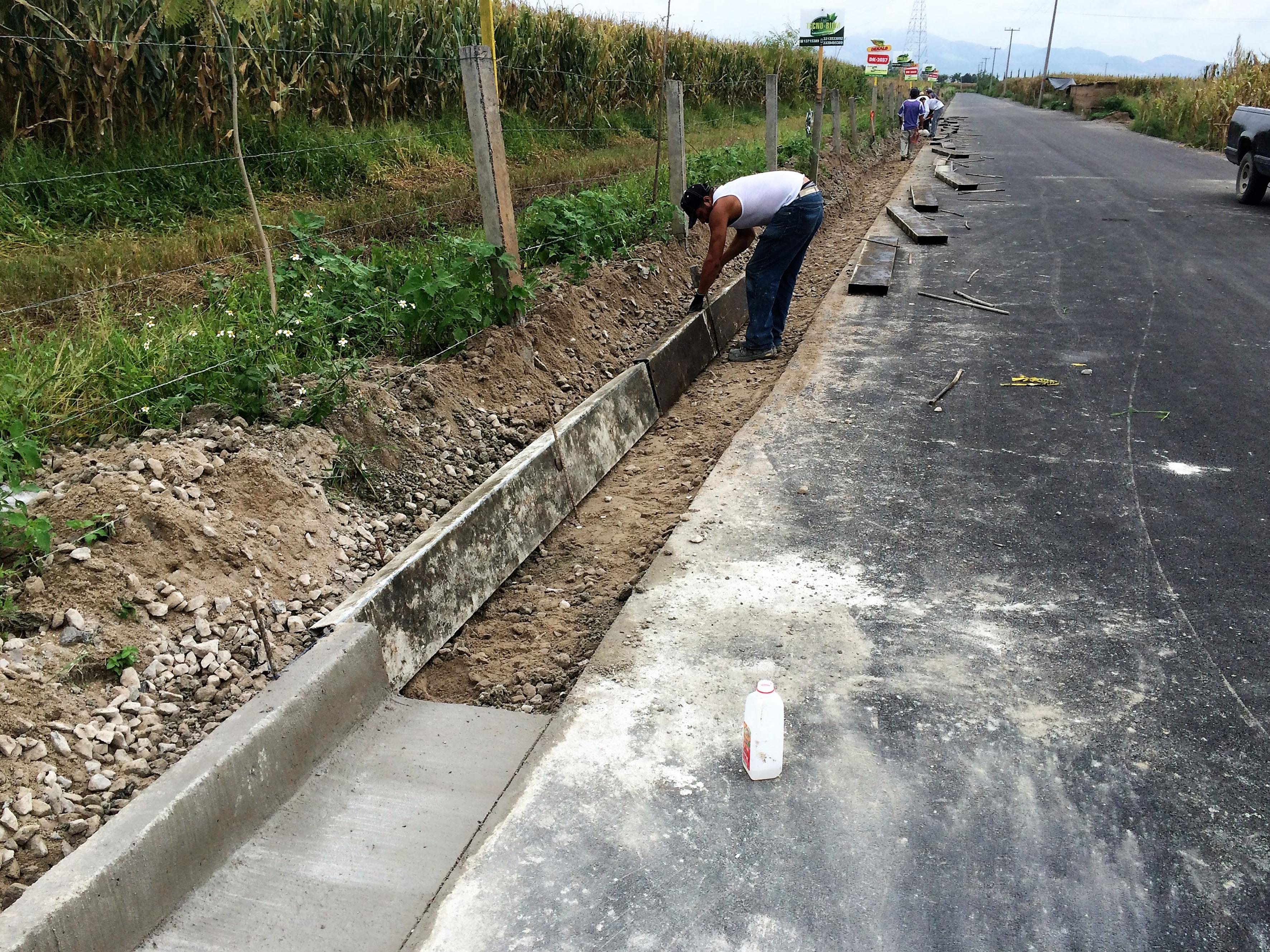 Trabajador de la obra apoyando en la pavimentación del tramo carretero
