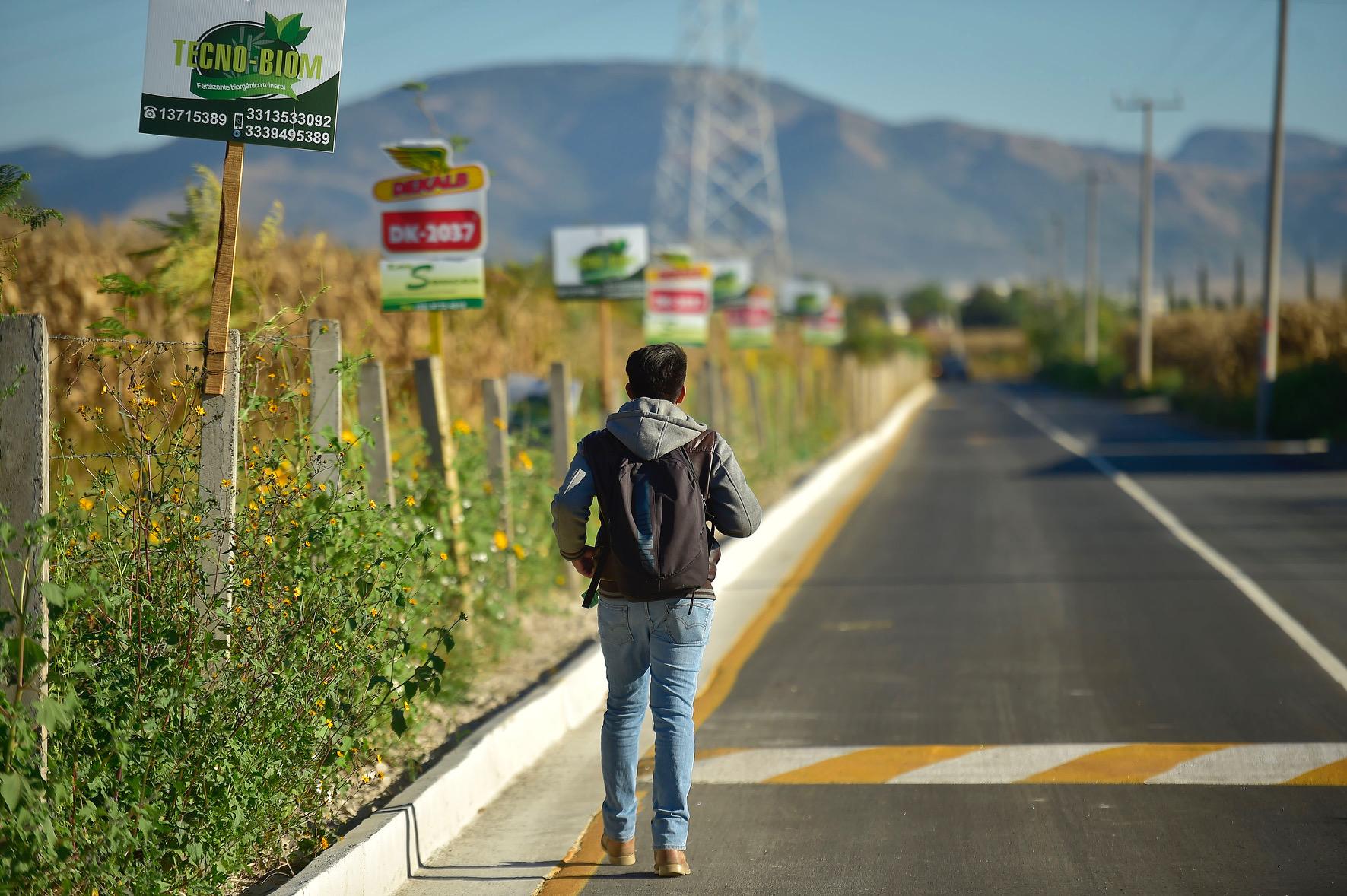 Aumno del Centro Universitario, caminando por el camino pavimentado