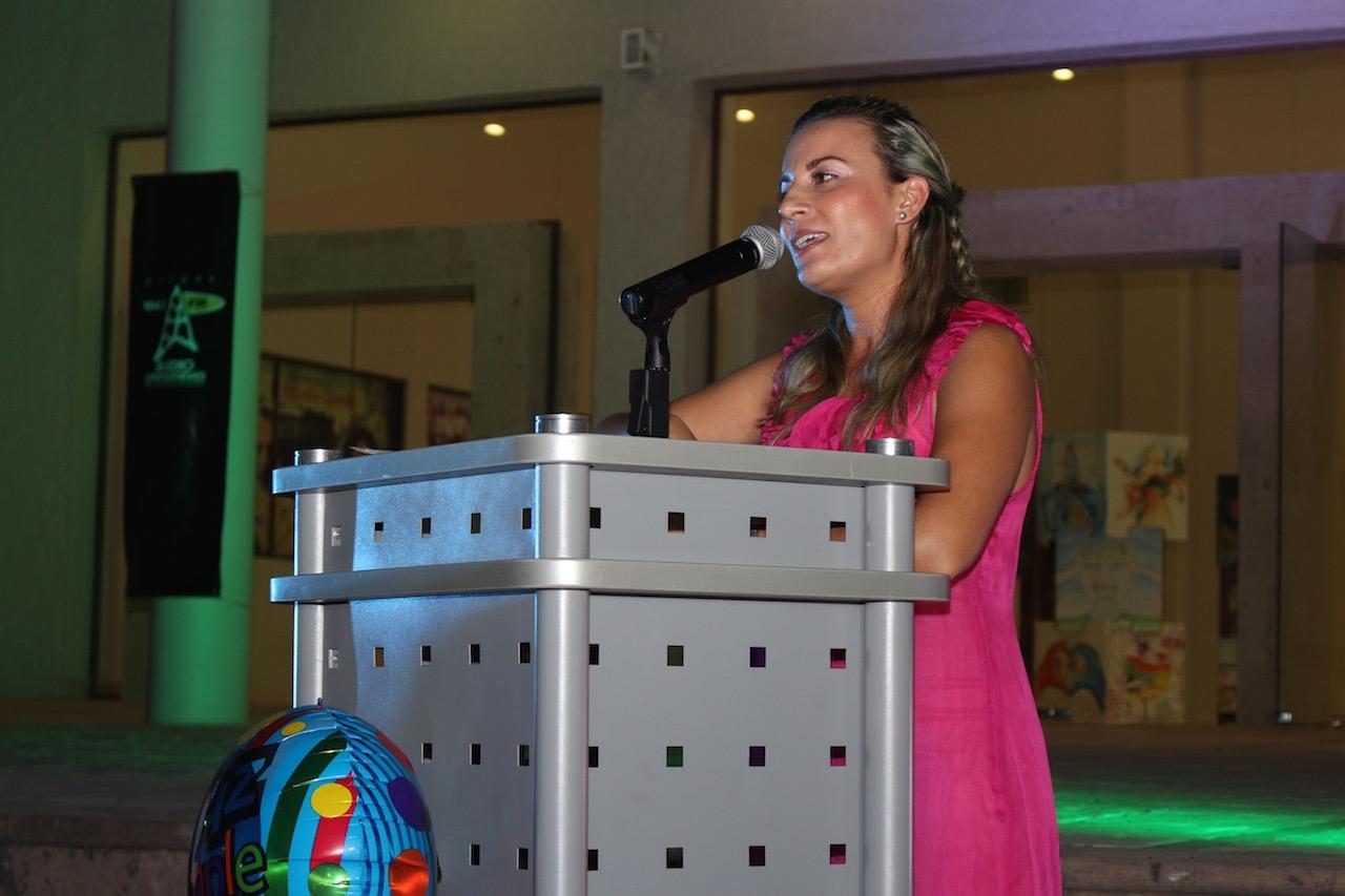 Licenciada Marina de los Santos Álvarez, subdirectora regional de Radio Universidad de Guadalajara en Puerto Vallarta, con micrófono en podium haciendo uso de la palabra.