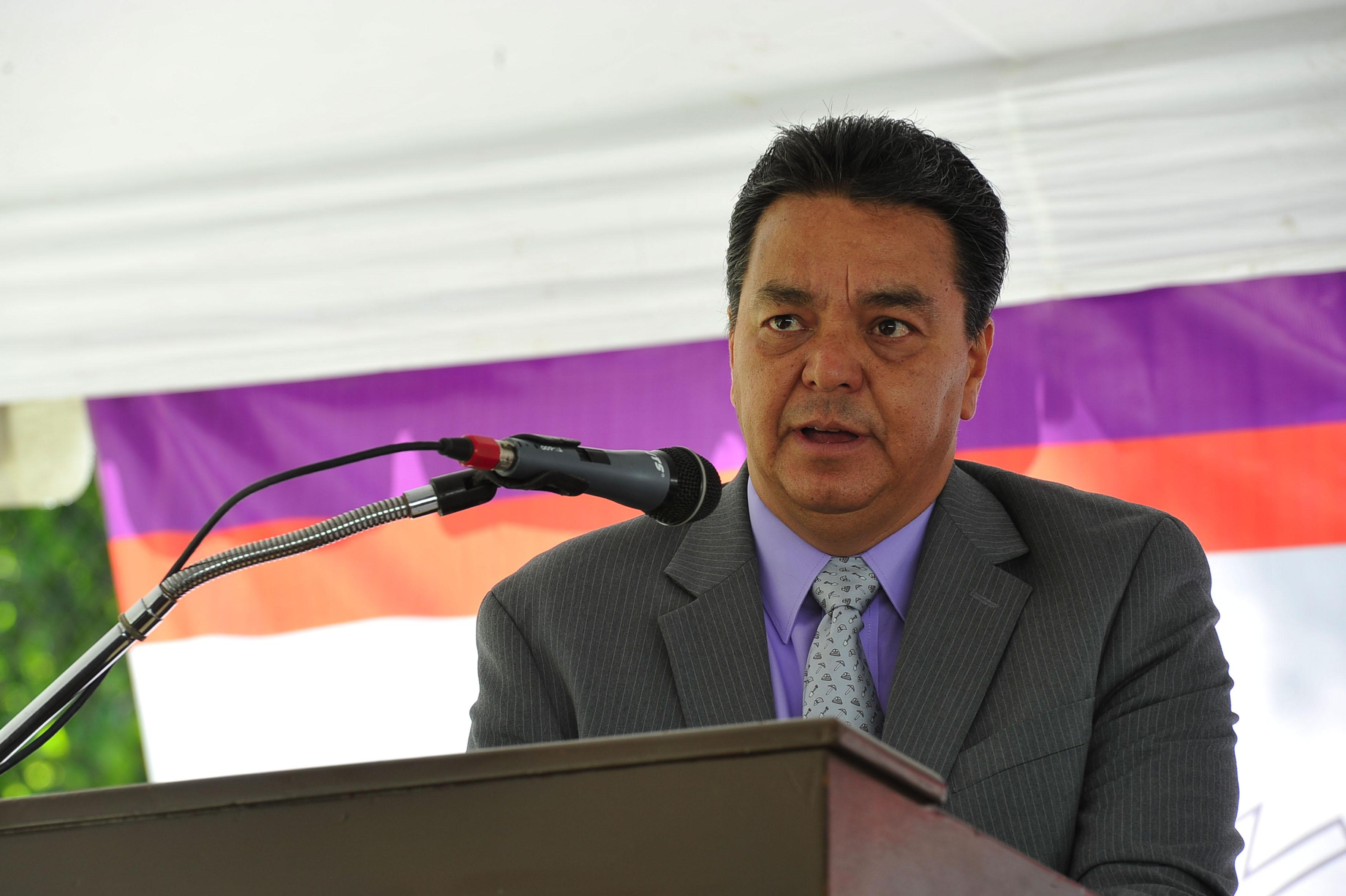 Maestro Rolando Castillo Murillo, director de la preparatoria Politécnica, con micrófono en podium haciendo uso de la palabra.