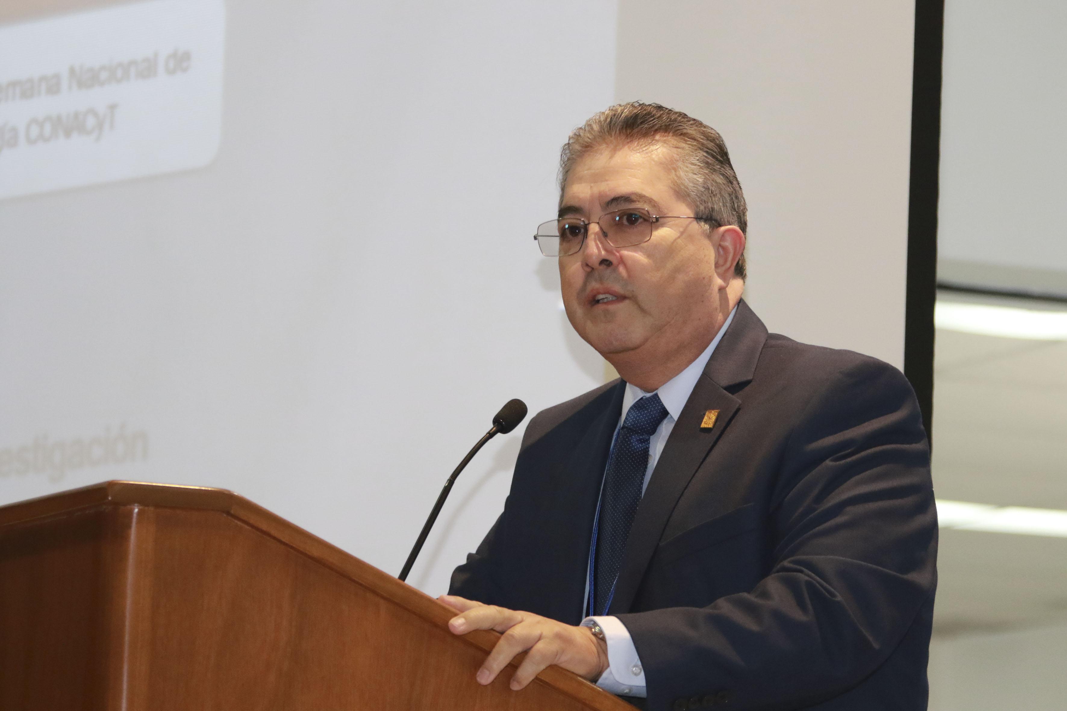 Doctor Carlos Beas Zárate, Rector del CUCBA, con micrófono en podium haciendo uso de la palabra.