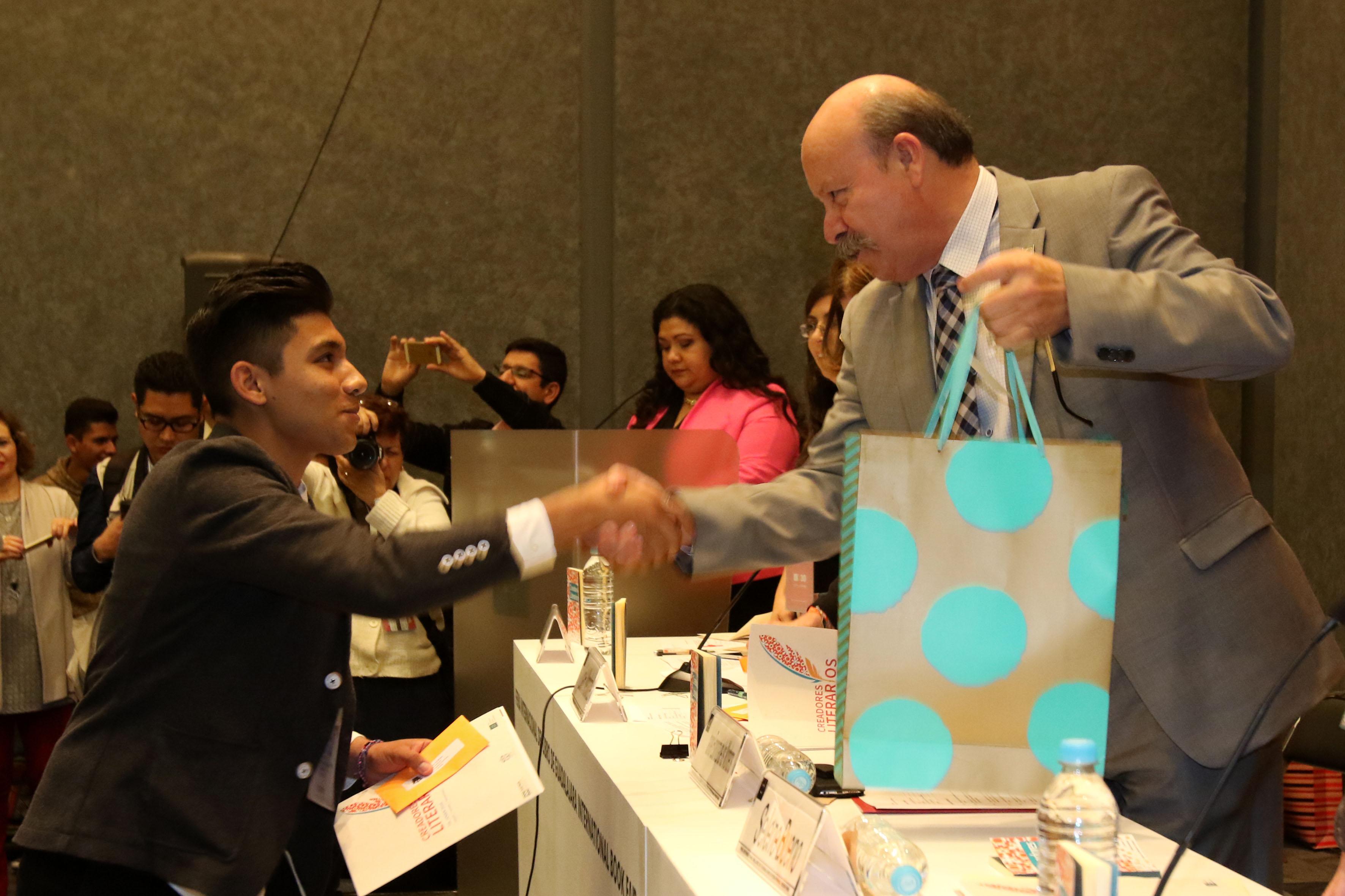 Director general del SEMS, maestro Javier Espinoza de los Monteros Cárdenas, felicitando y entregando regalo a ganador del concurso.