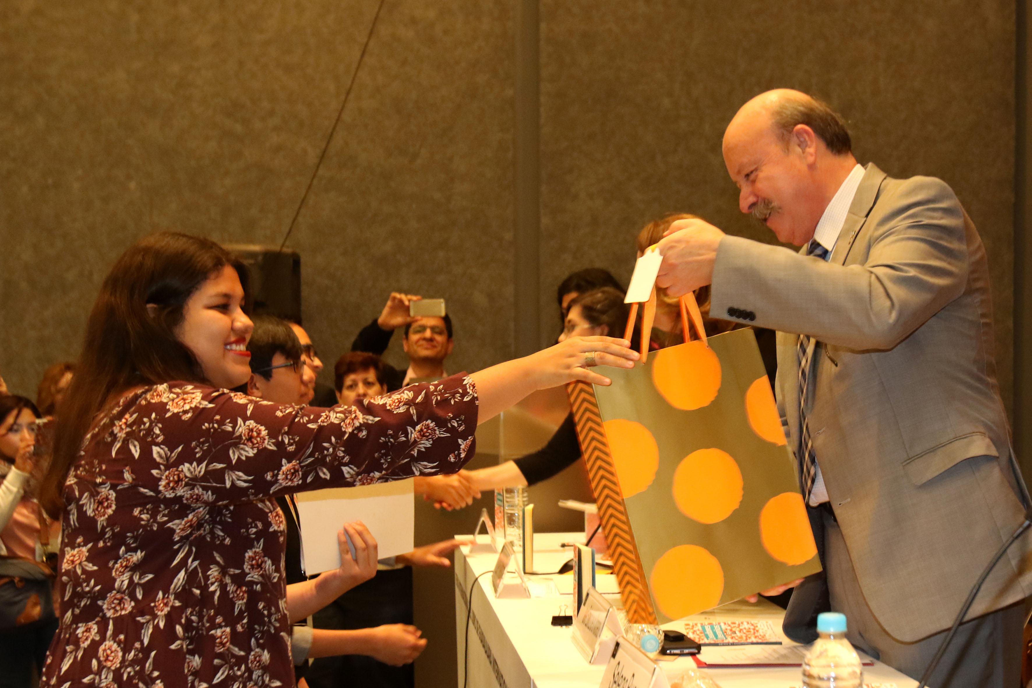 Director general del SEMS, maestro Javier Espinoza de los Monteros Cárdenas, felicitando y entregando regalo a ganadora del concurso.