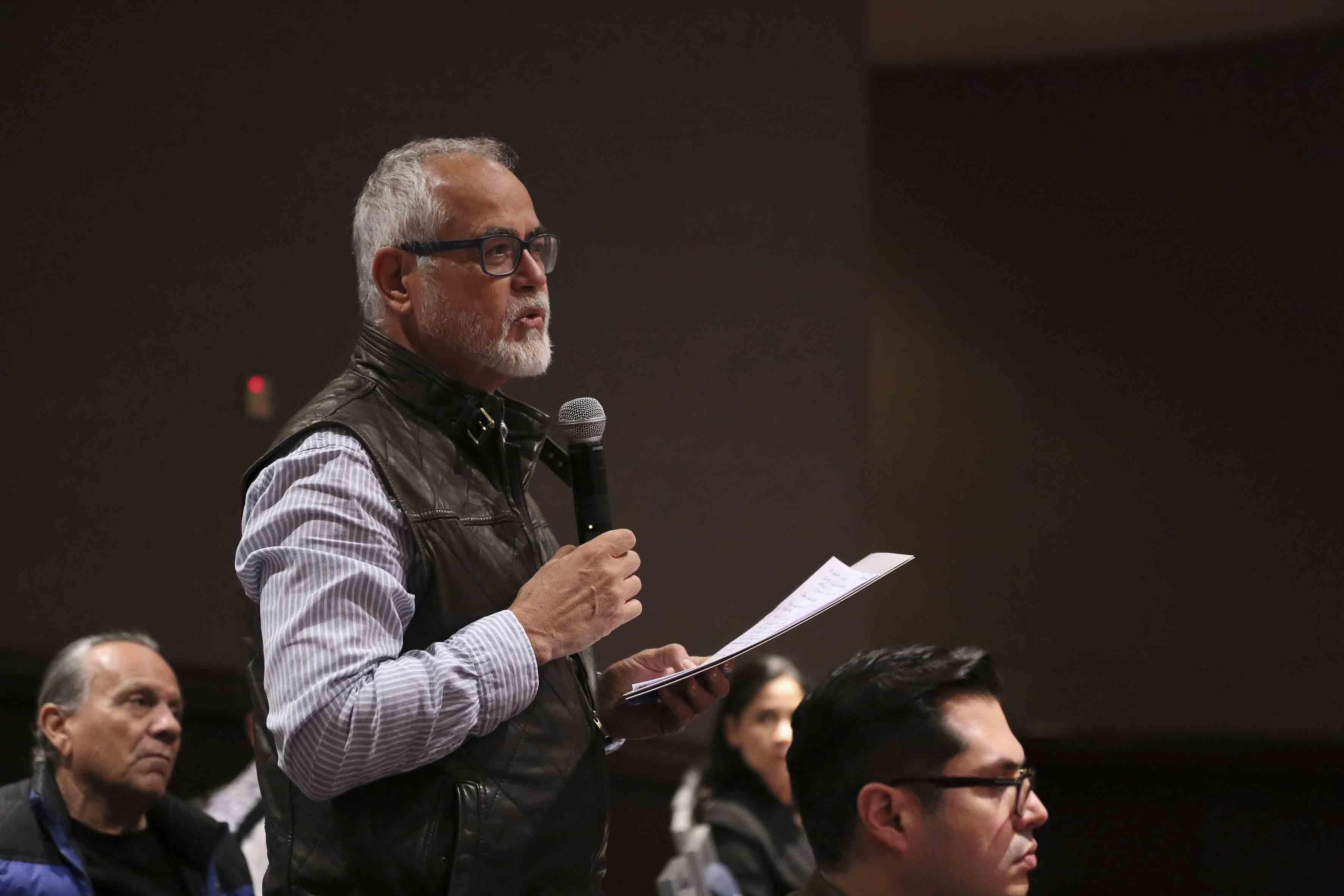 Persona del público, con micrófono en mano, haciendo preguntas a los panelistas en el Foro de cambi climático.
