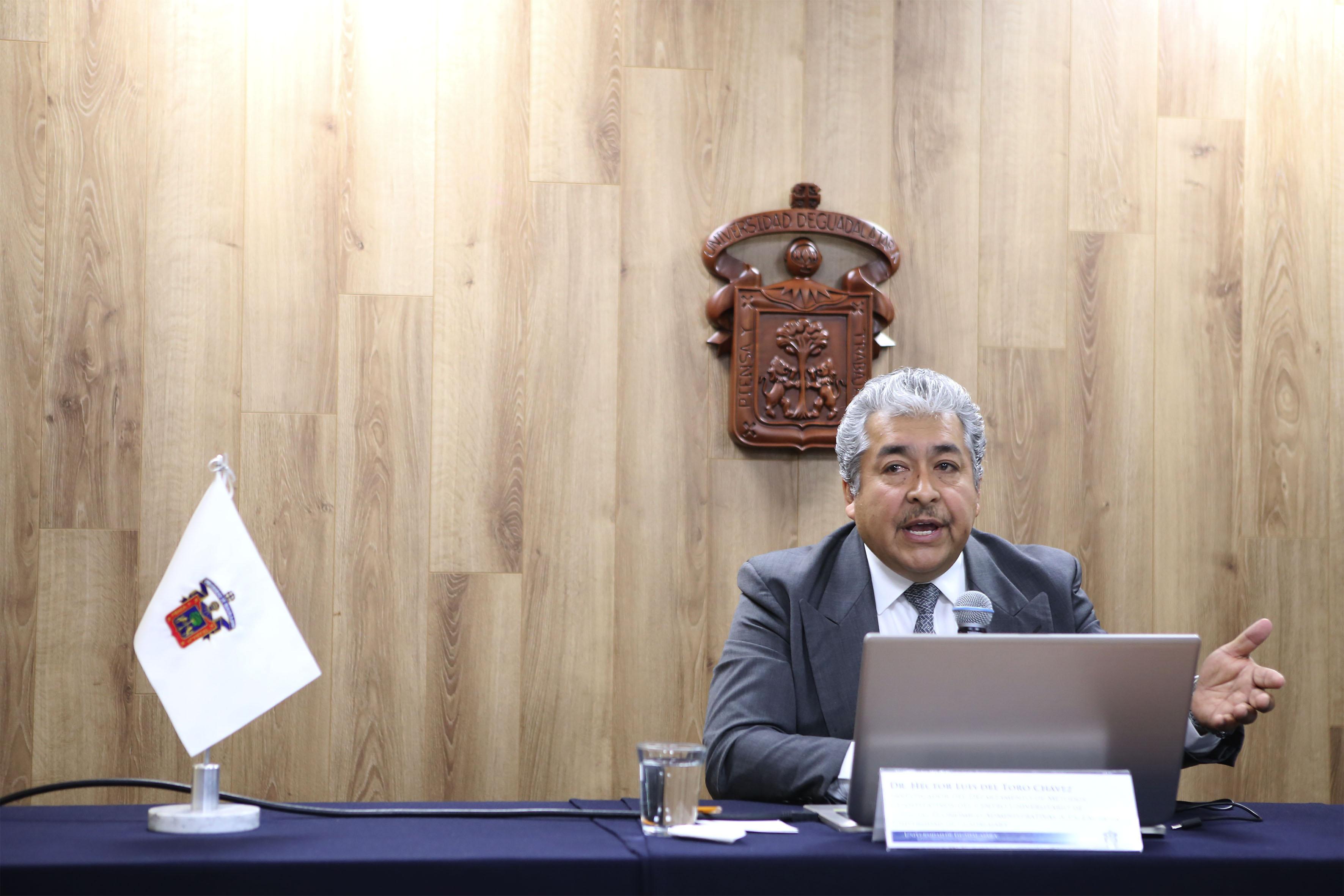 Doctor Héctor Luis del Toro Chávez, investigador del Centro Universitario de Ciencias Económico Administrativas de la Universidad de Guadalajara, con micrófono en mano haciendo uso de la palabra para dar a conocer los resultados de su investigación Canasta Básica e Índice Precios en la Zona Metropolitana de Guadalajara.