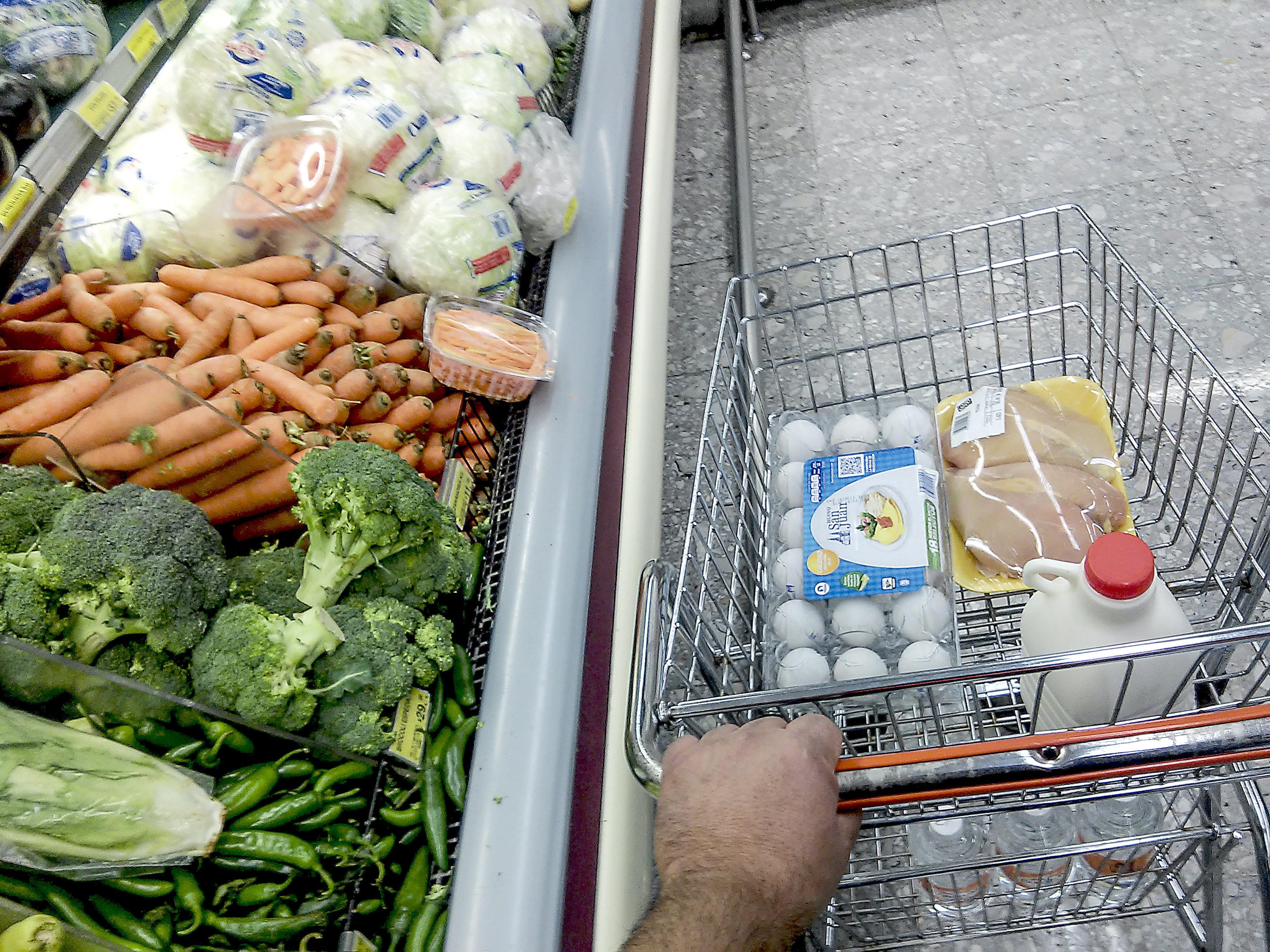 Persona empujando carrito de mercado con productos de canasta básica como: huevo, leche y pollo, dentro de tienda departamental.