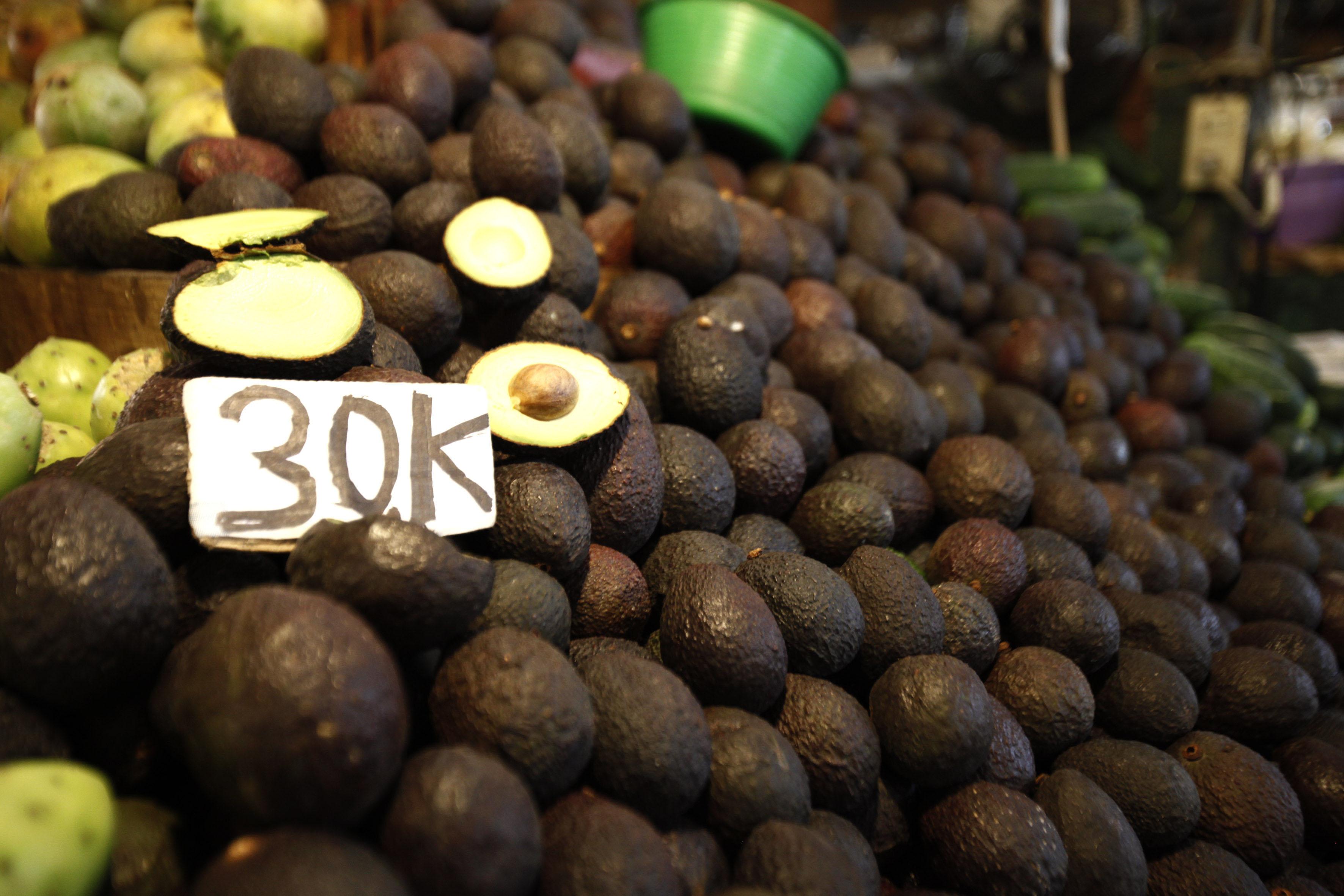 Pila de aguacates en mercado local, donde se muestra el precio por kilo del producto.
