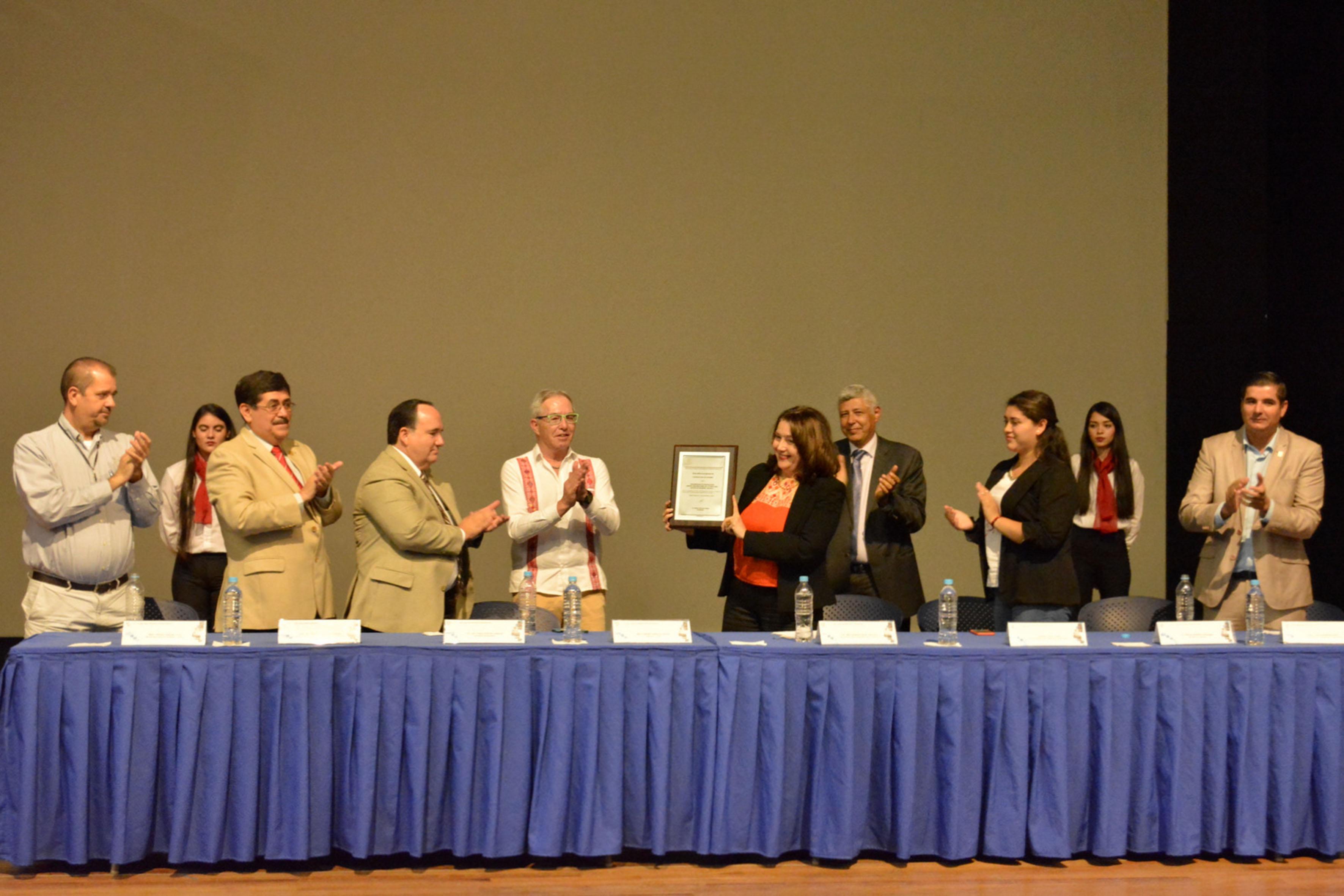 Doctora Lilia Victoria Oliver Sánchez, Rectora del CUCSur, mostrando constancia recibida de reacreditación como programa de calidad por parte del Conaet, mientras asistentes a acto protocolario aplauden.