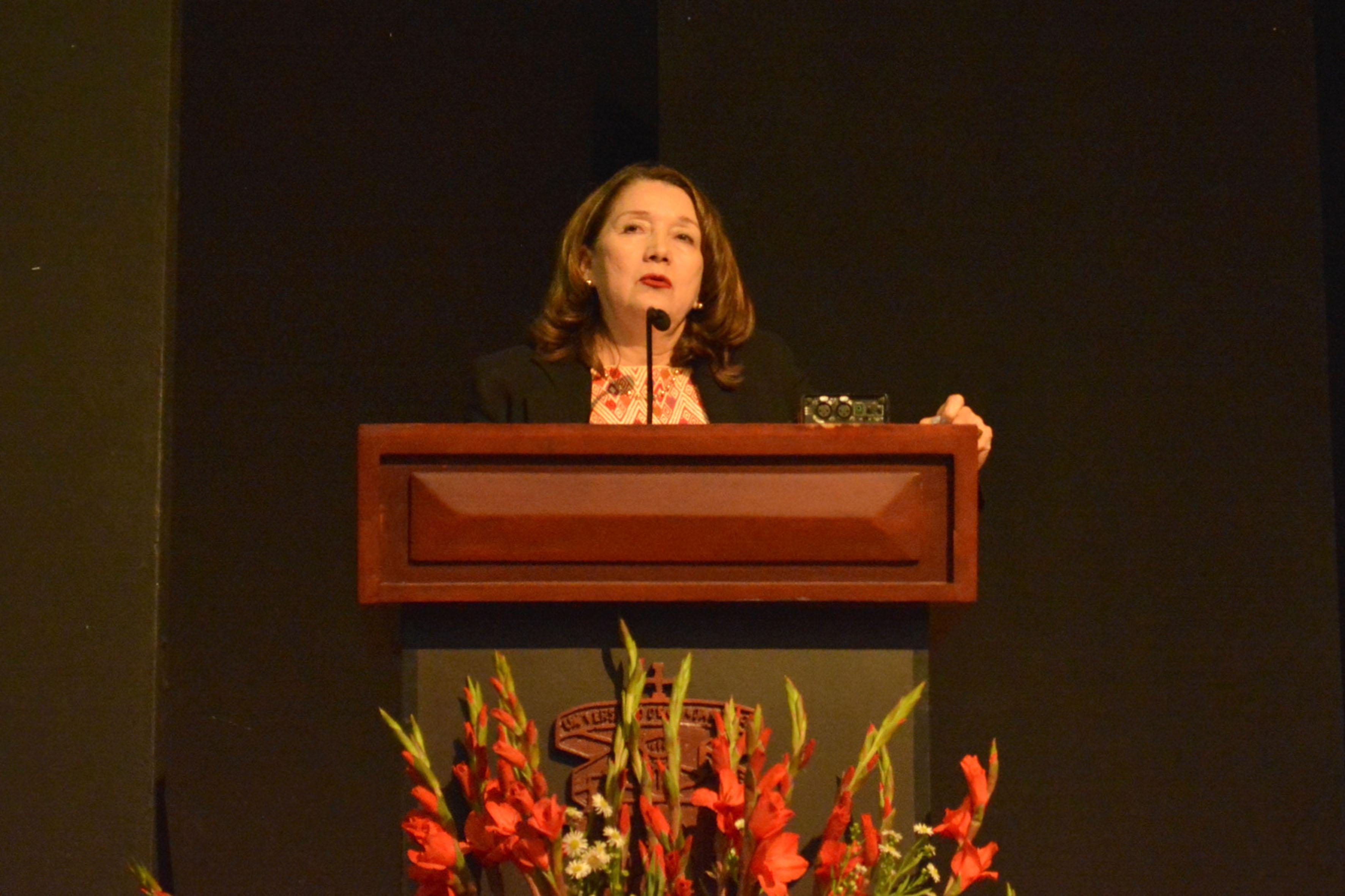 Doctora Lilia Victoria Oliver Sánchez, Rectora del CUCSur, en podium haciendo uso de la palabra, durante acto protocolario.