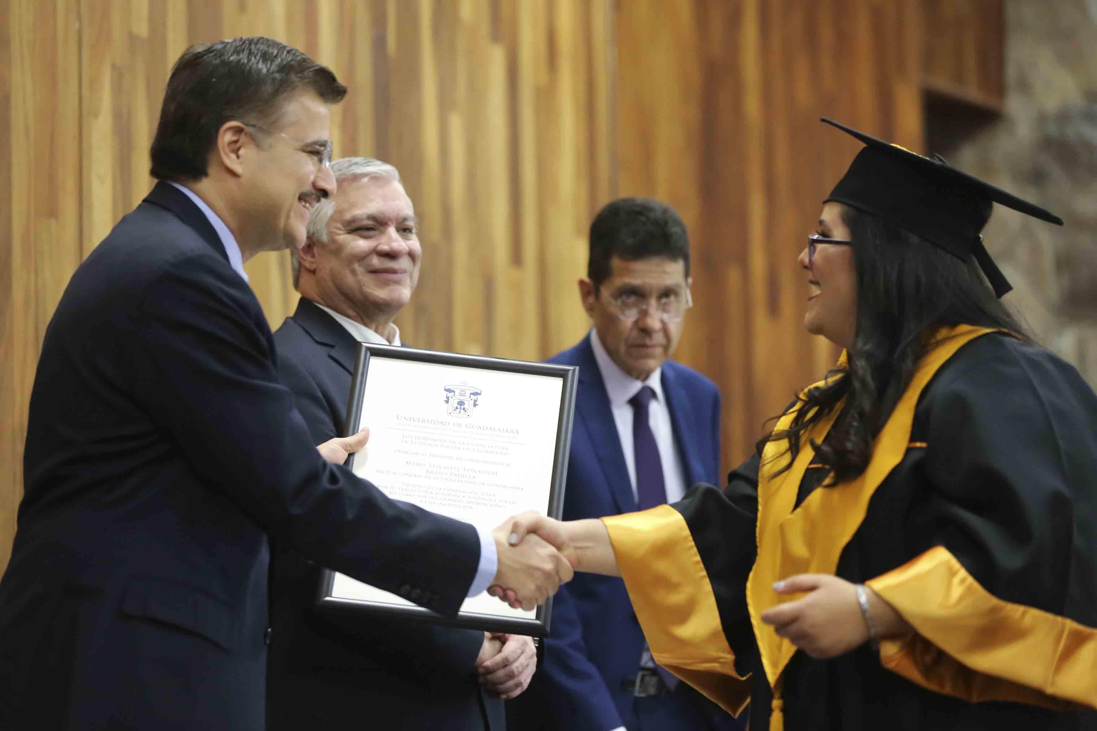Maestro Itzcóatl Tonatiuh Bravo Padilla, Rector General de la Universidad de Guadalajara, entregando reconocimientos a egresados de la carrera de Estudios Políticos y Gobierno, en acto protocolario en el Paraninfo Enrique Díaz de Léon.