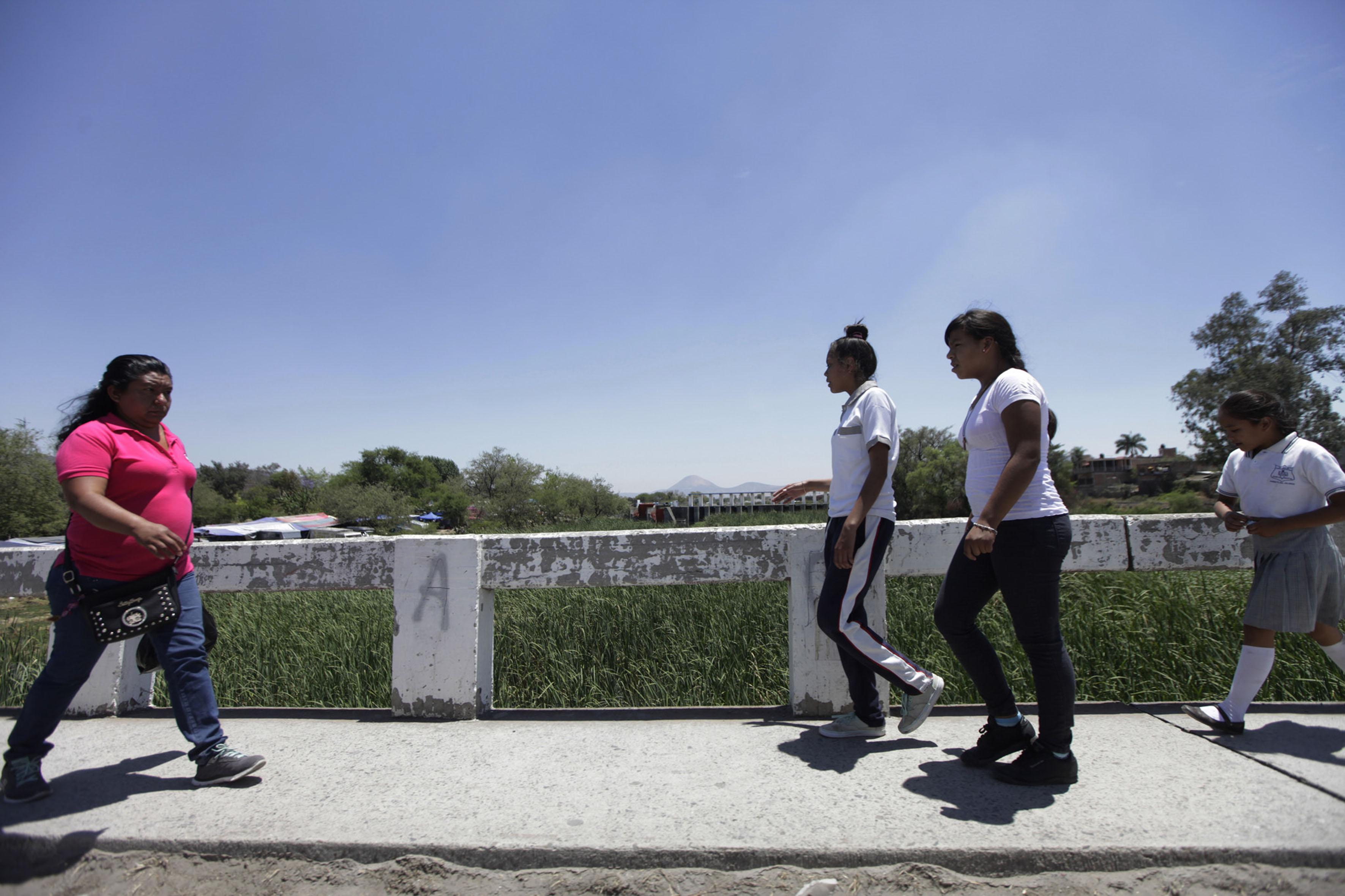 Personas caminando sobre puente peatonal ubicado en el rio verde.