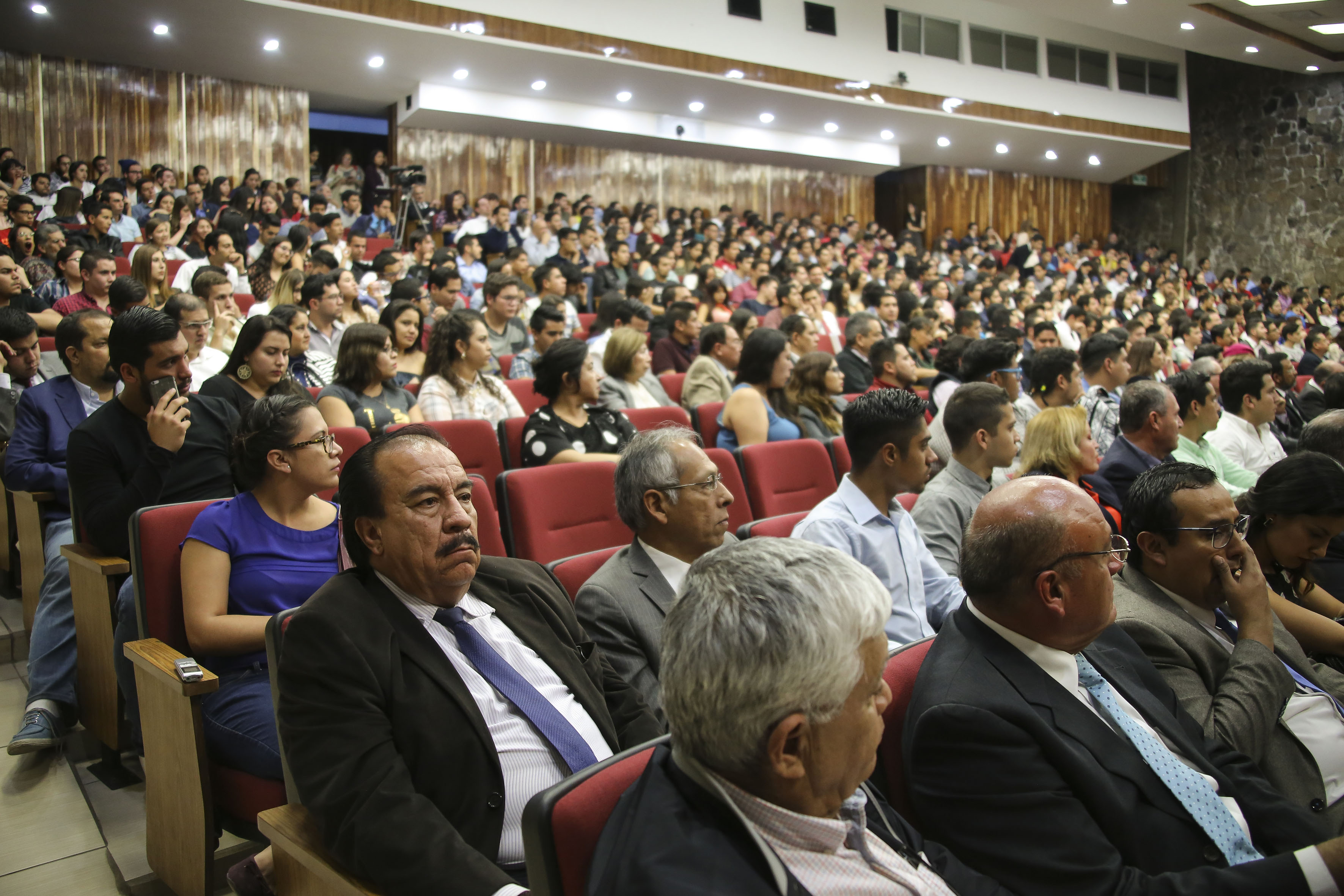 Publico asistente a la Ponente hablando frente al microfono en la Ceremonia de conmemoración por el 100 aniversario de la promulgación de la Constitución Política de los Estados Unidos Mexicanos y del Estado de Jalisco
