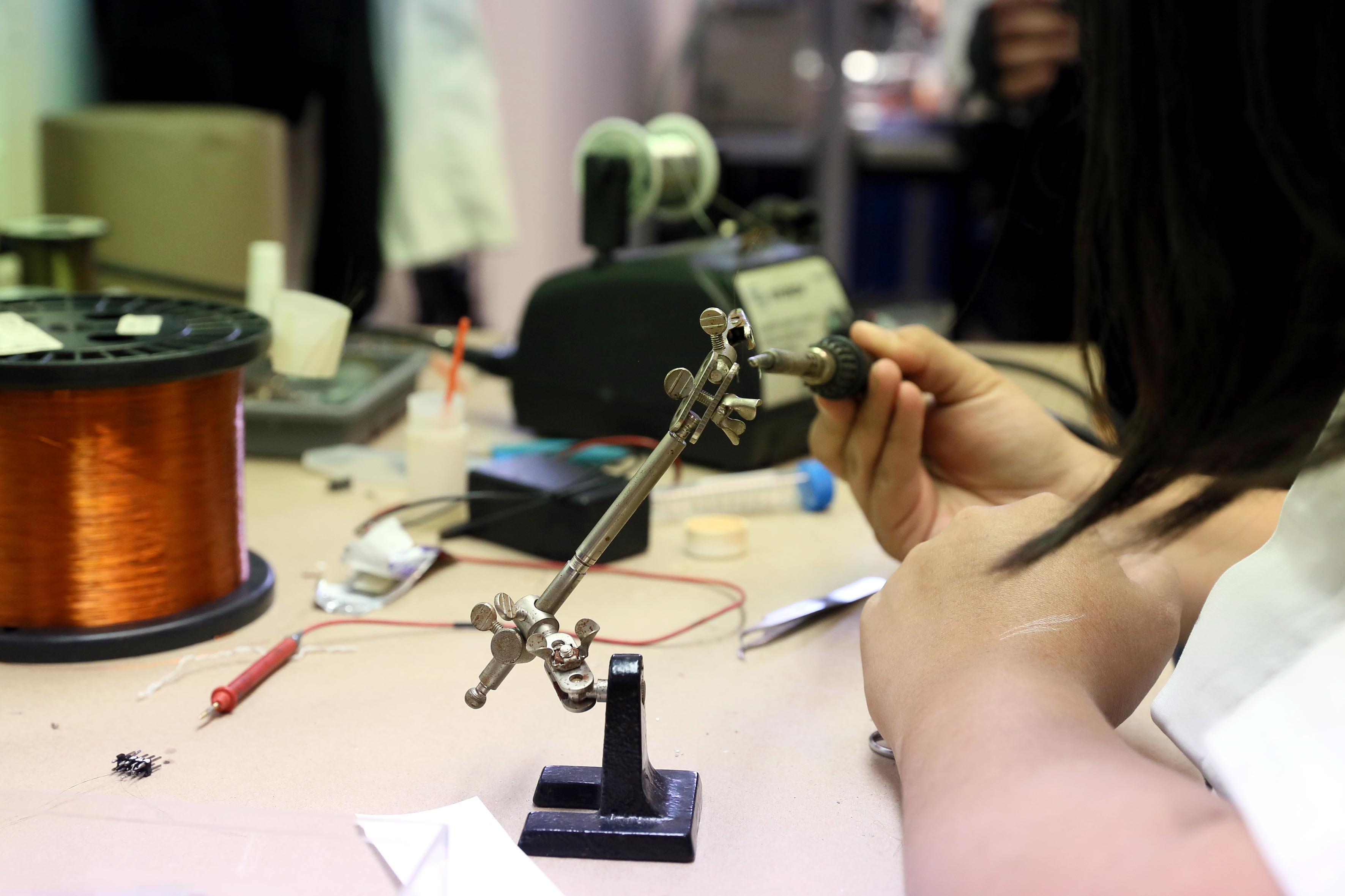 Investigadora maniobrando equipo eléctrico para pruebas de laboratorio.