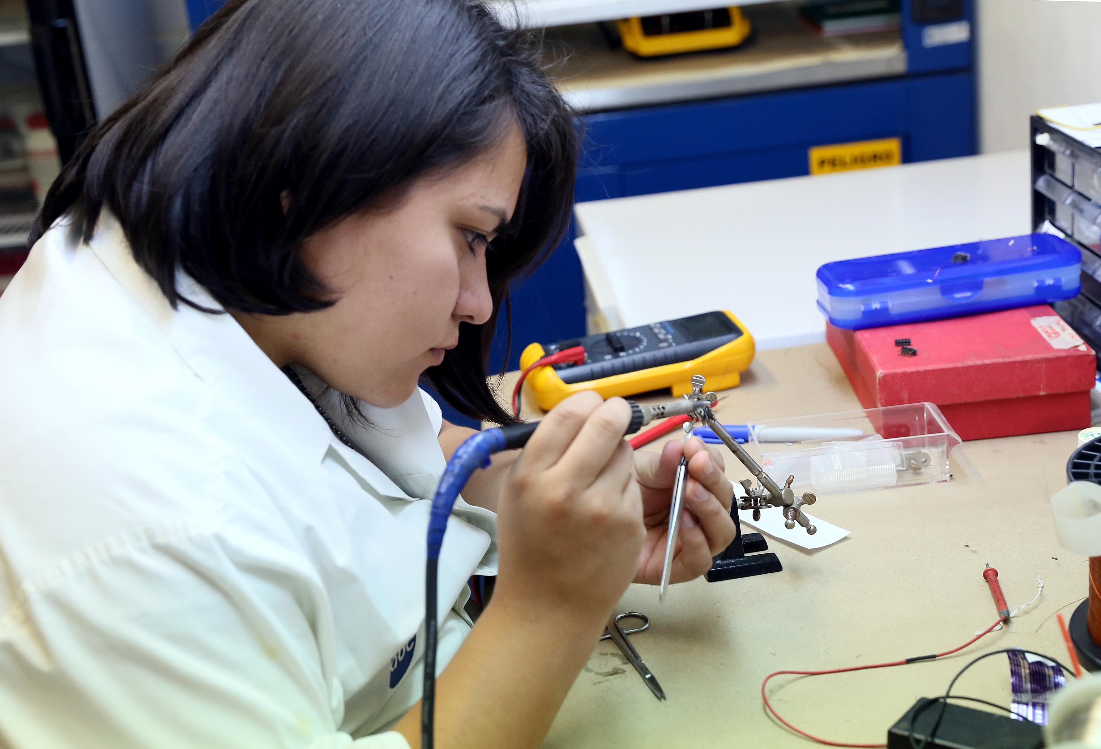 Investigadora del CUCB, maniobrando equipo eléctrico para pruebas de laboratorio.