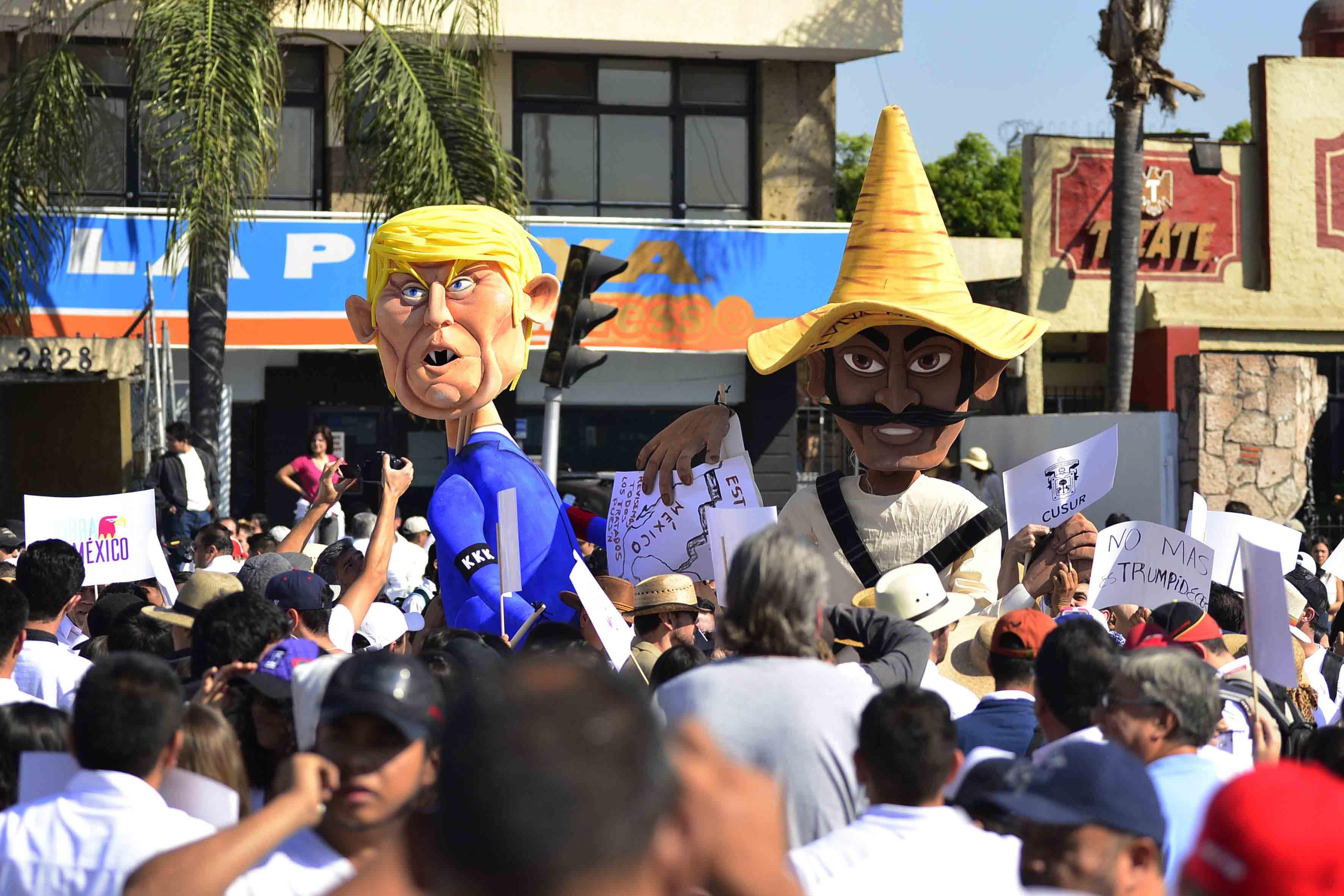 Manifestantes portando muñeco de cartón de Donald Trump