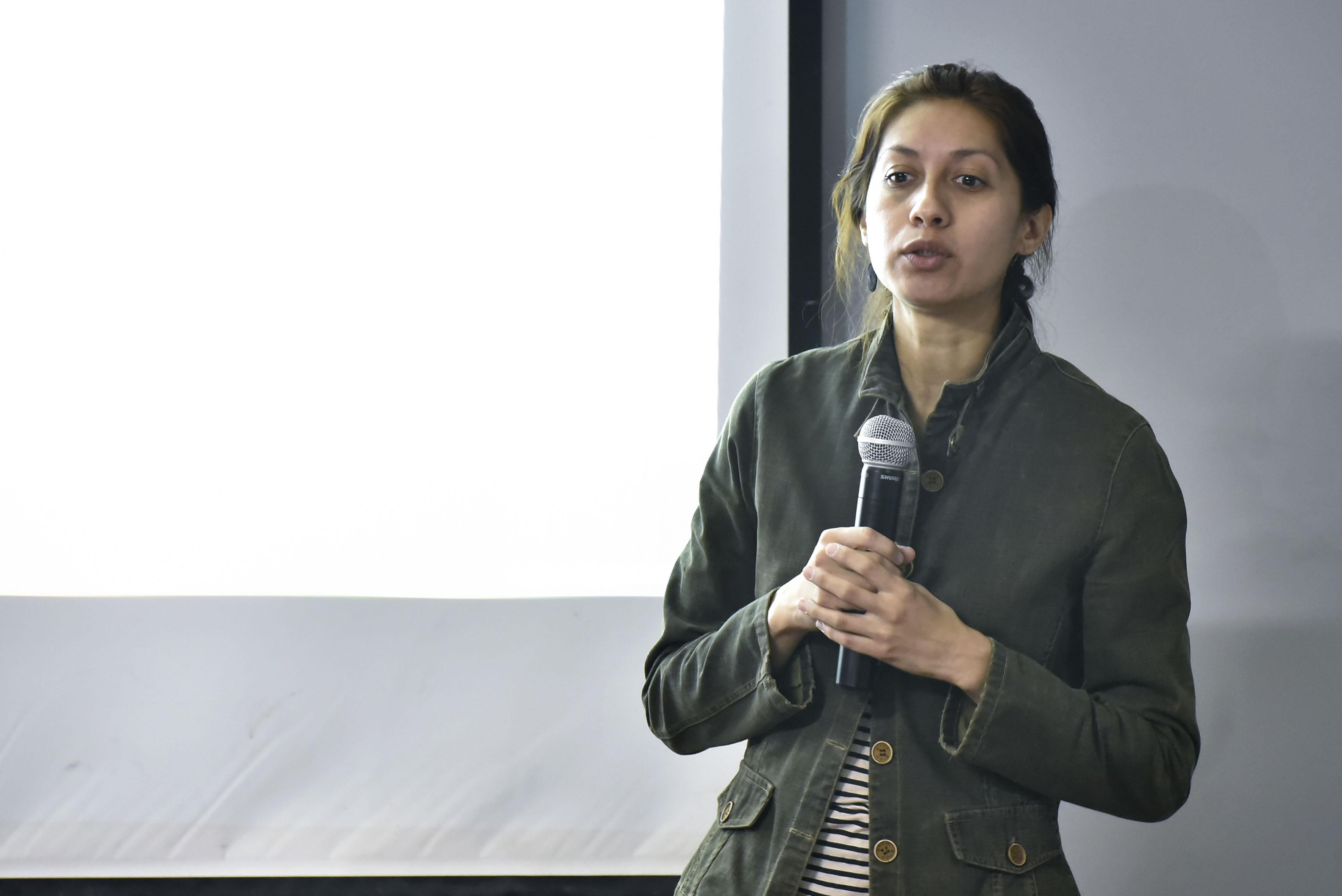 Perla Berenice Sánchez Torres, estudiante de la maestría en Ciencias de la Salud Ambiental del Centro Universitario de Ciencias Biológicas y Ambientales, con micrófono en mano haciendo uso de la palabra.