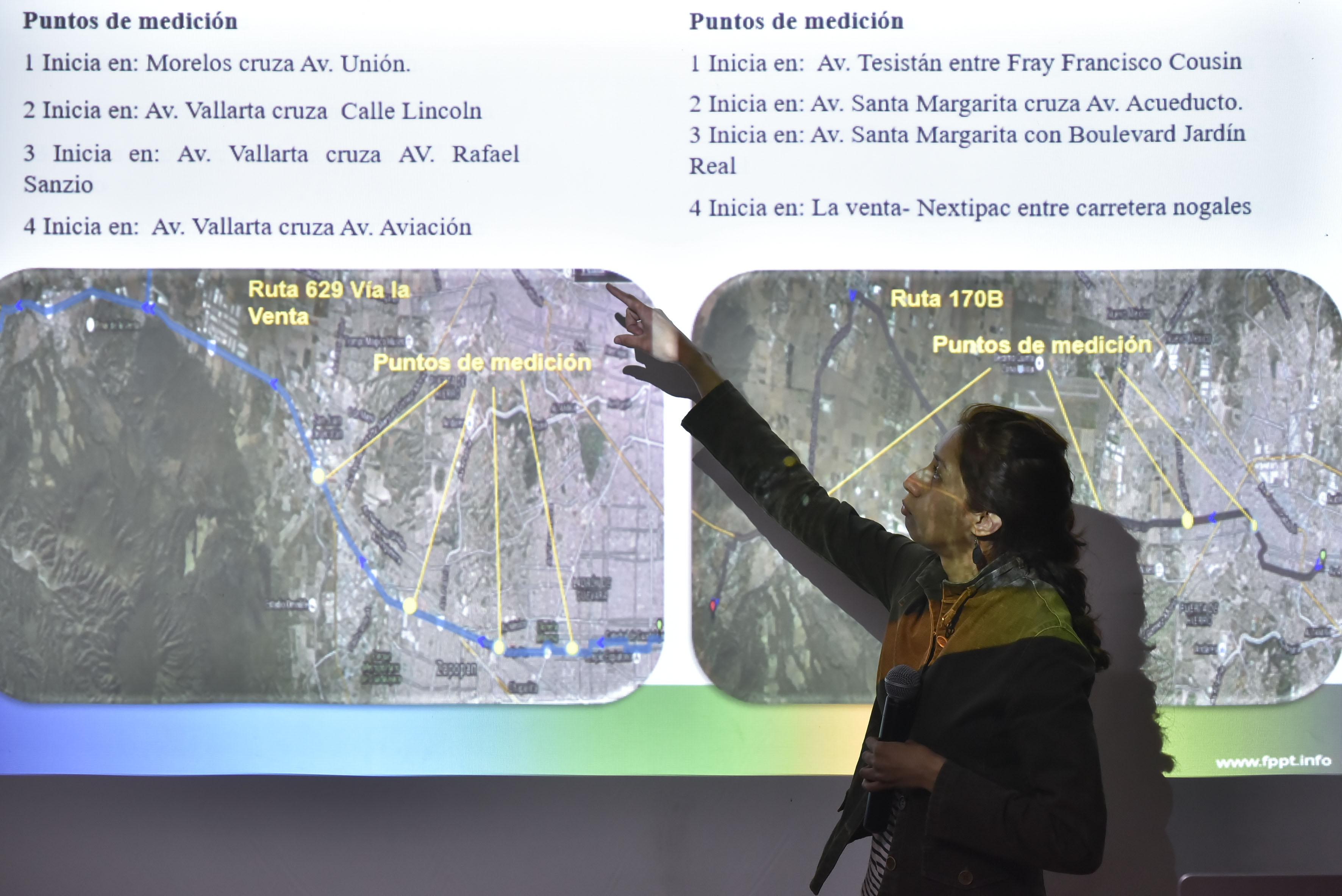 Perla Berenice Sánchez Torres, estudiante de la maestría en Ciencias de la Salud Ambiental del Centro Universitario de Ciencias Biológicas y Ambientales, señalando un mapa de rutas de camión y puntos de medición, durante su exposición