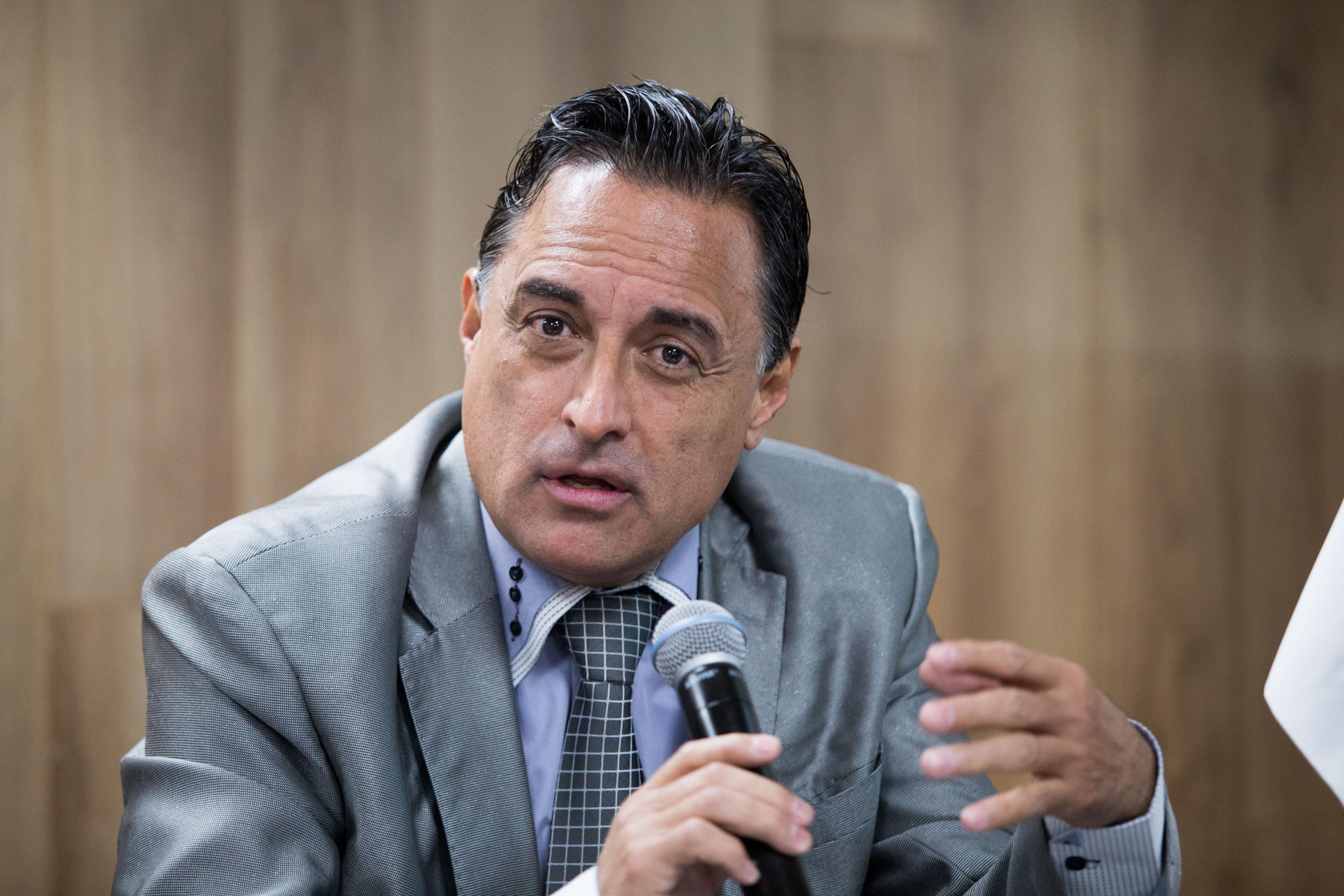 Doctor Carlos Benítez Sánchez, integrante del comité del colegio; con micrófono en mano, haciendo uso de la palabra.