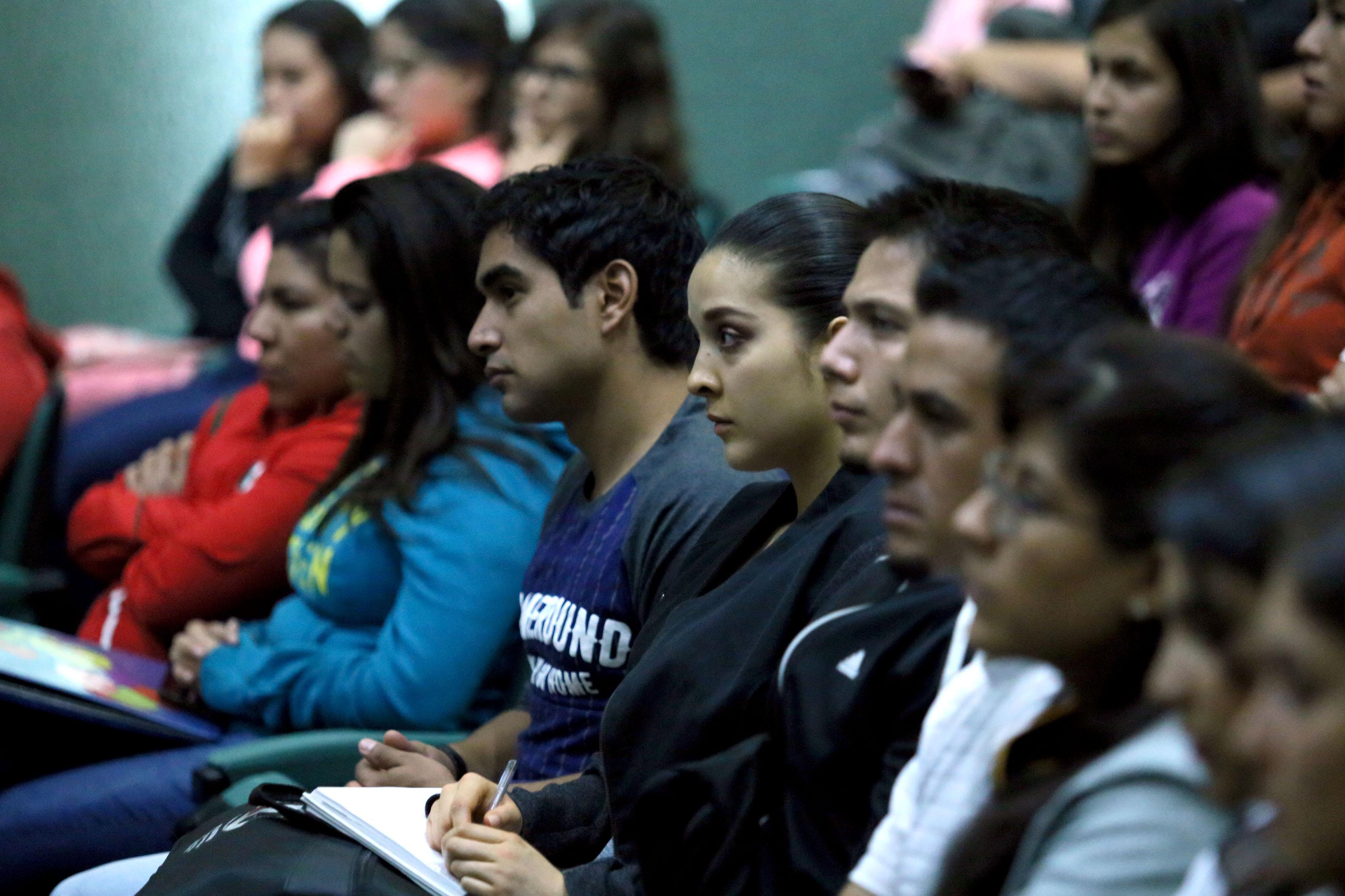 personas poniendo atencion a conferencia en foro universitario